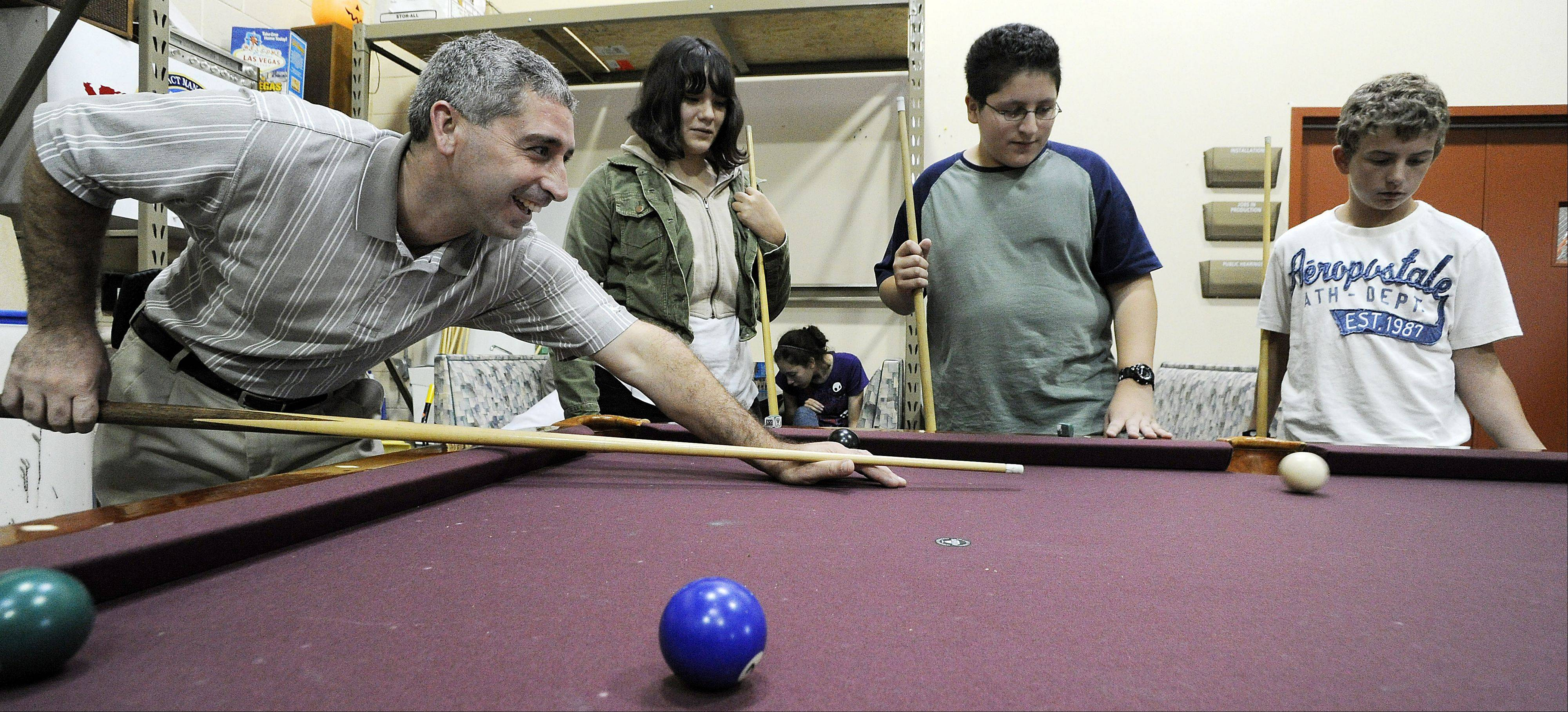 Philip Herman, executive director of the Greater Wheeling Area Youth Organization, shoots pool with students in 2011 when the group's center opened in Arlington Heights. Herman is leaving the organization to pursue full-time work as a youth minister.