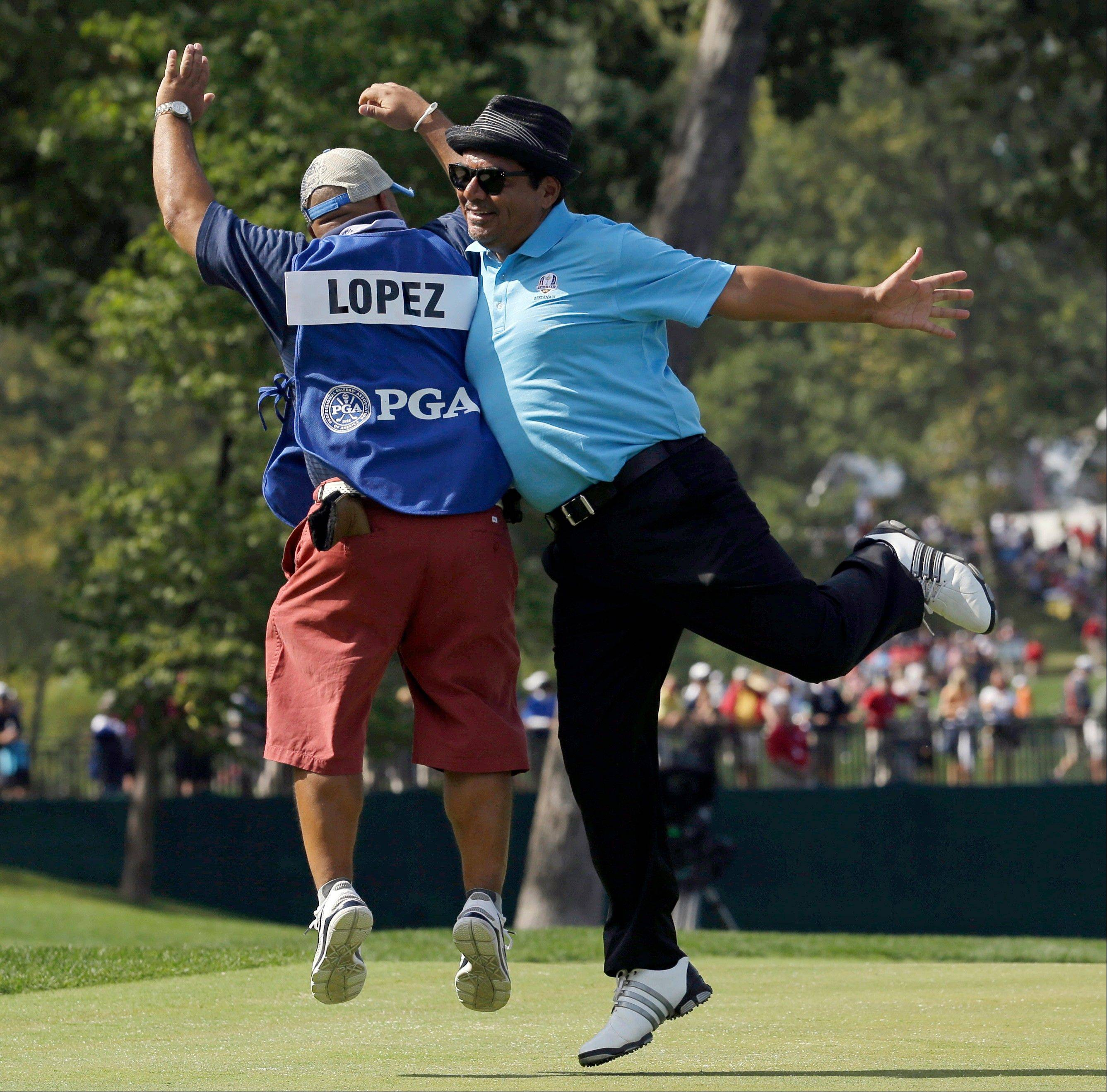 Comedian George Lopez, right, celebrates with his caddie after making a putt on the second hole.