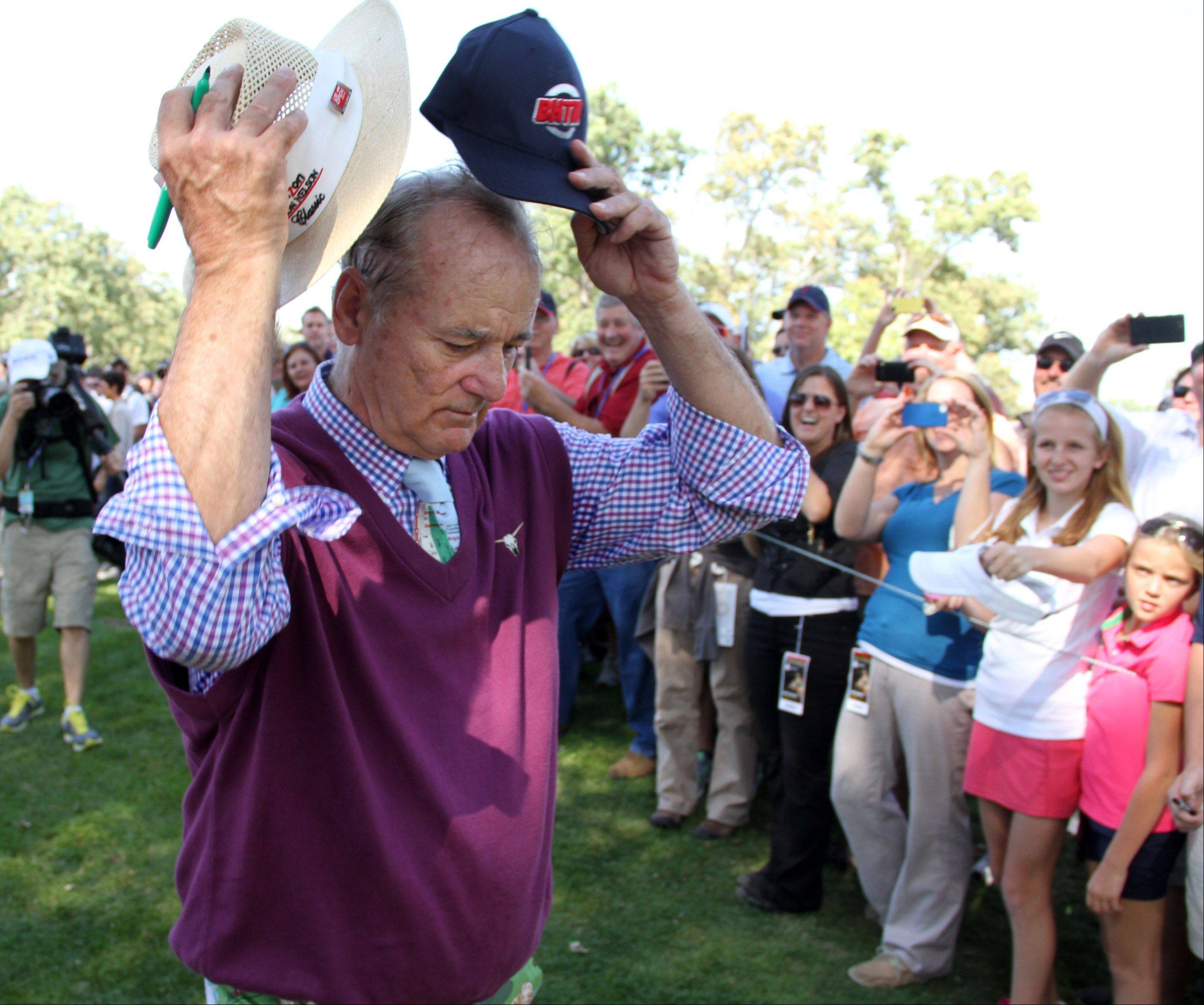 Bill Murray tries on a fans hat before offering an autograph.