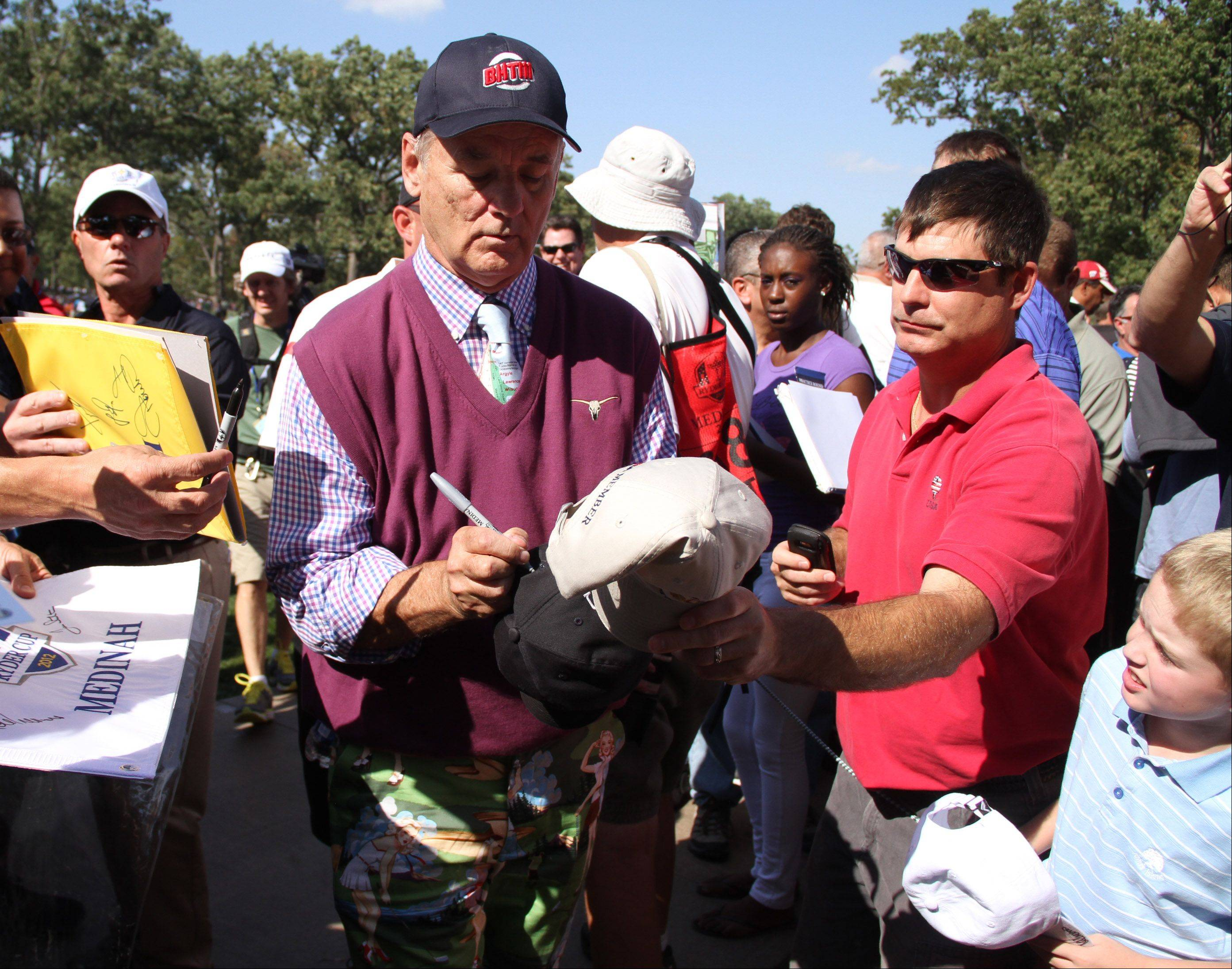 Bill Murray signs autographs while walking the course.