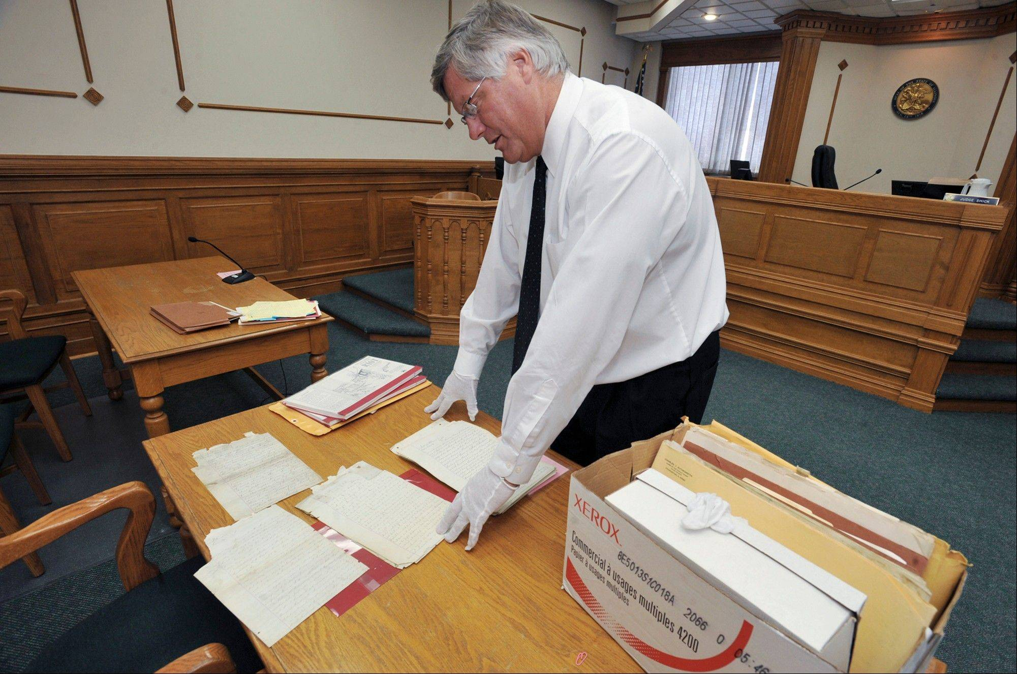 Judge Mitch Shick looks at sworn statements from Charleston Riot witnesses and participants as he spreads them out on a table at the Coles County Courthouse in Charleston.