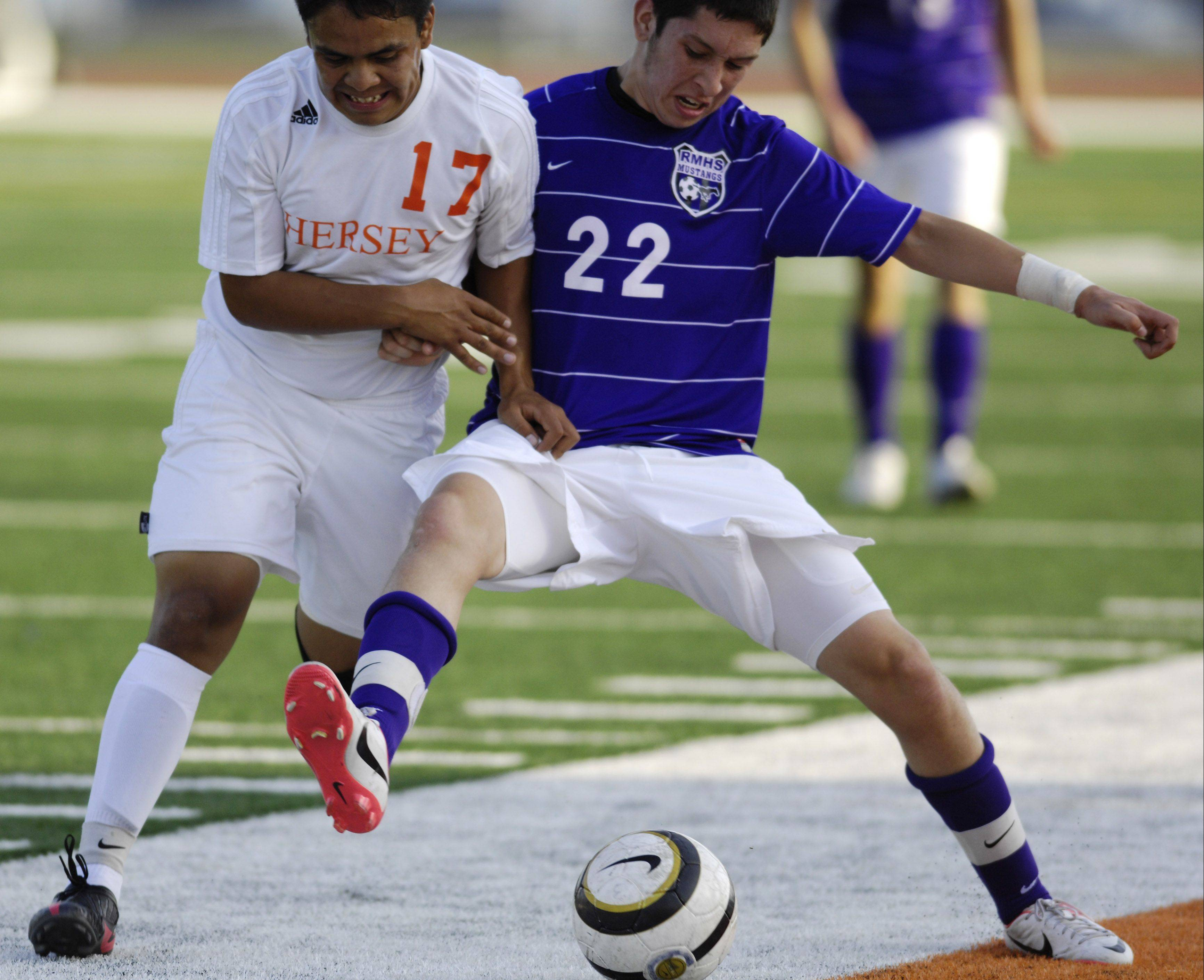 Hersey's Ben Juarez, left, and Rolling Meadows' Freddy Zarate battle for position along the sideline during Tuesday's game.
