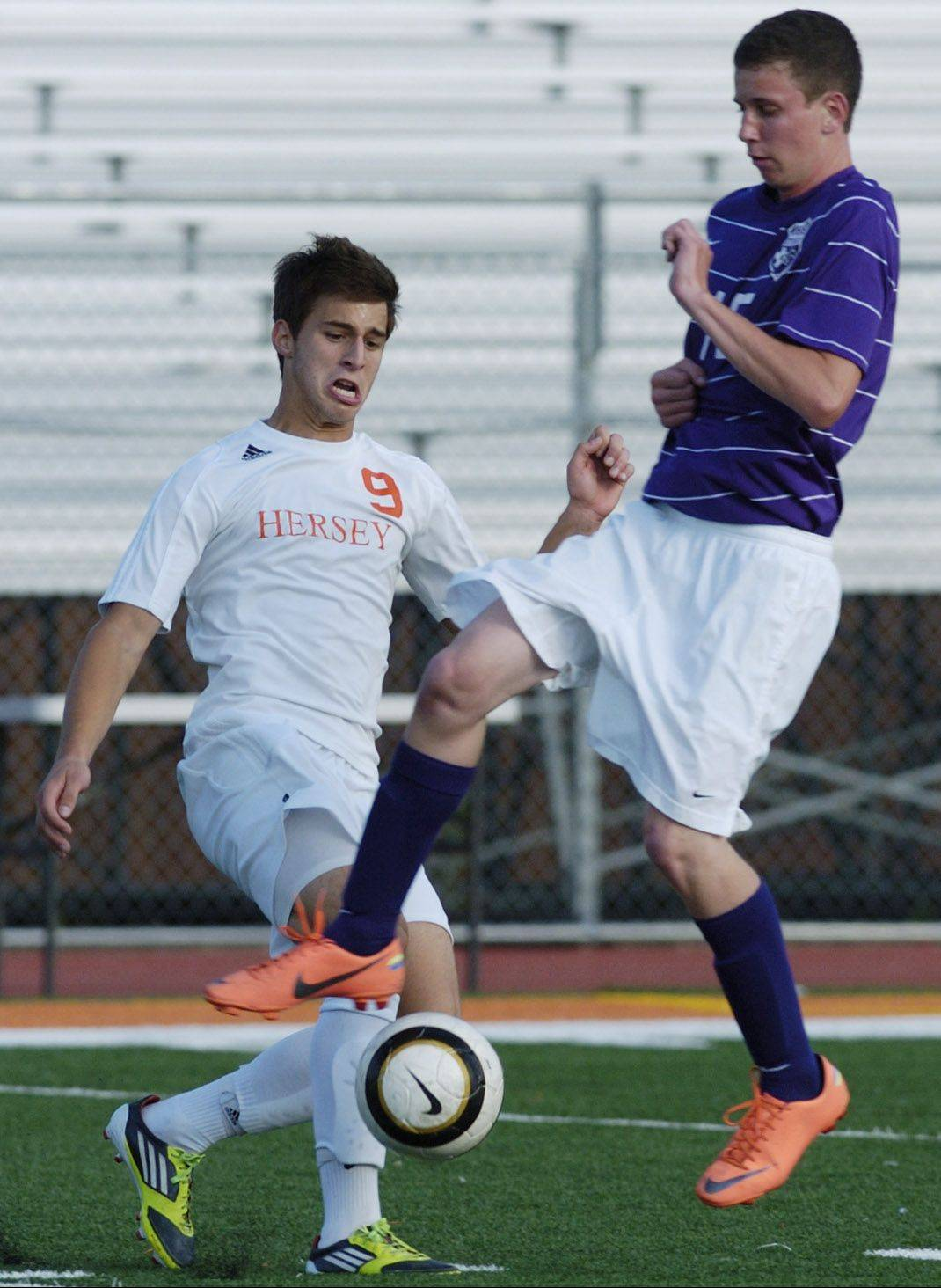 Rolling Meadows' Tim Smith, right, tries to knock the ball down in front of Hersey's Nikola Vukovic on Tuesday.
