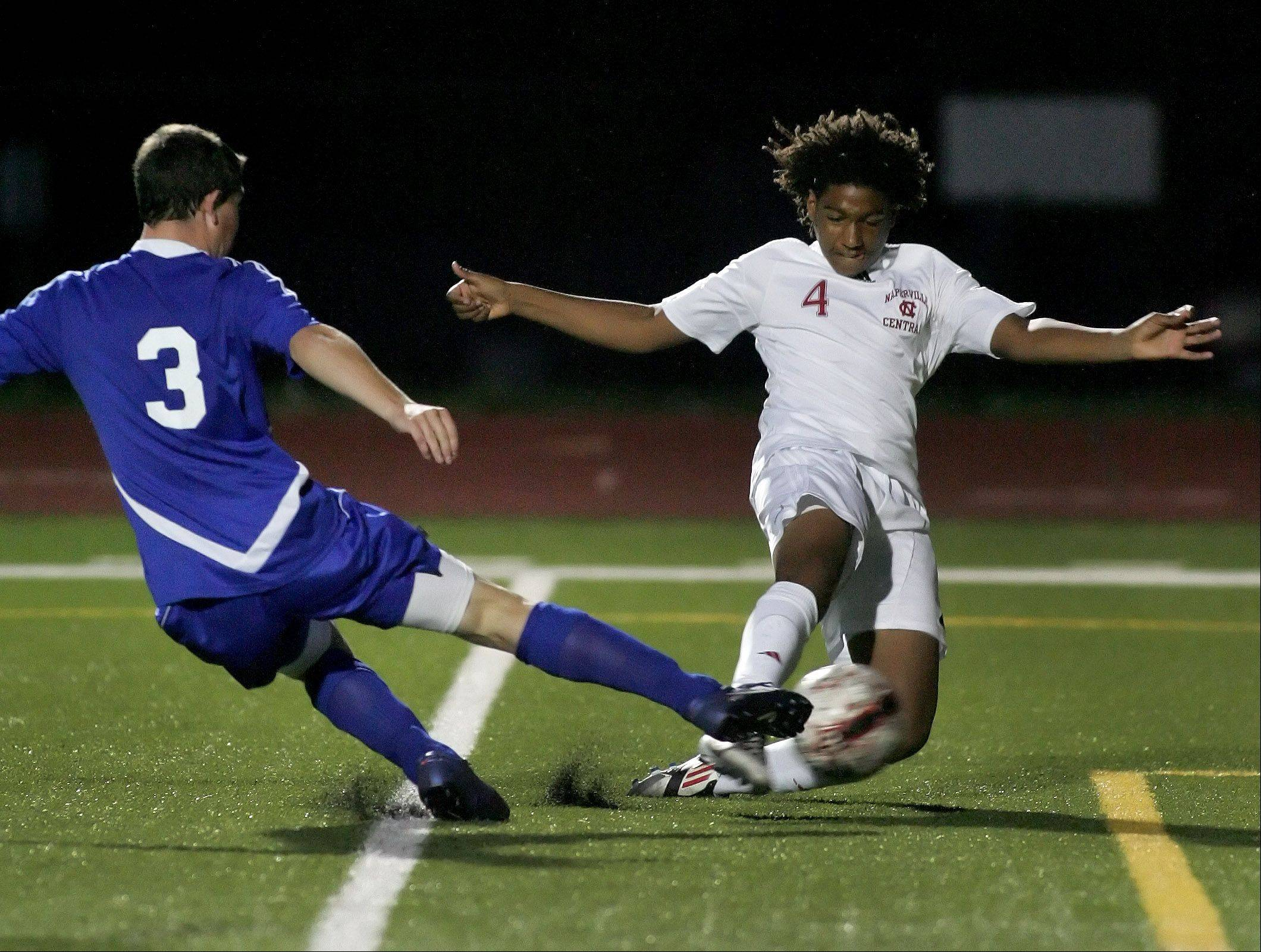Bev Horne/bhorne@dailyherald.comDevon Amoo-Mensah, right, of Naperville Central, takes control of the ball from Brian Pfaff of Wheaton North and scores on Tuesday in Naperville.