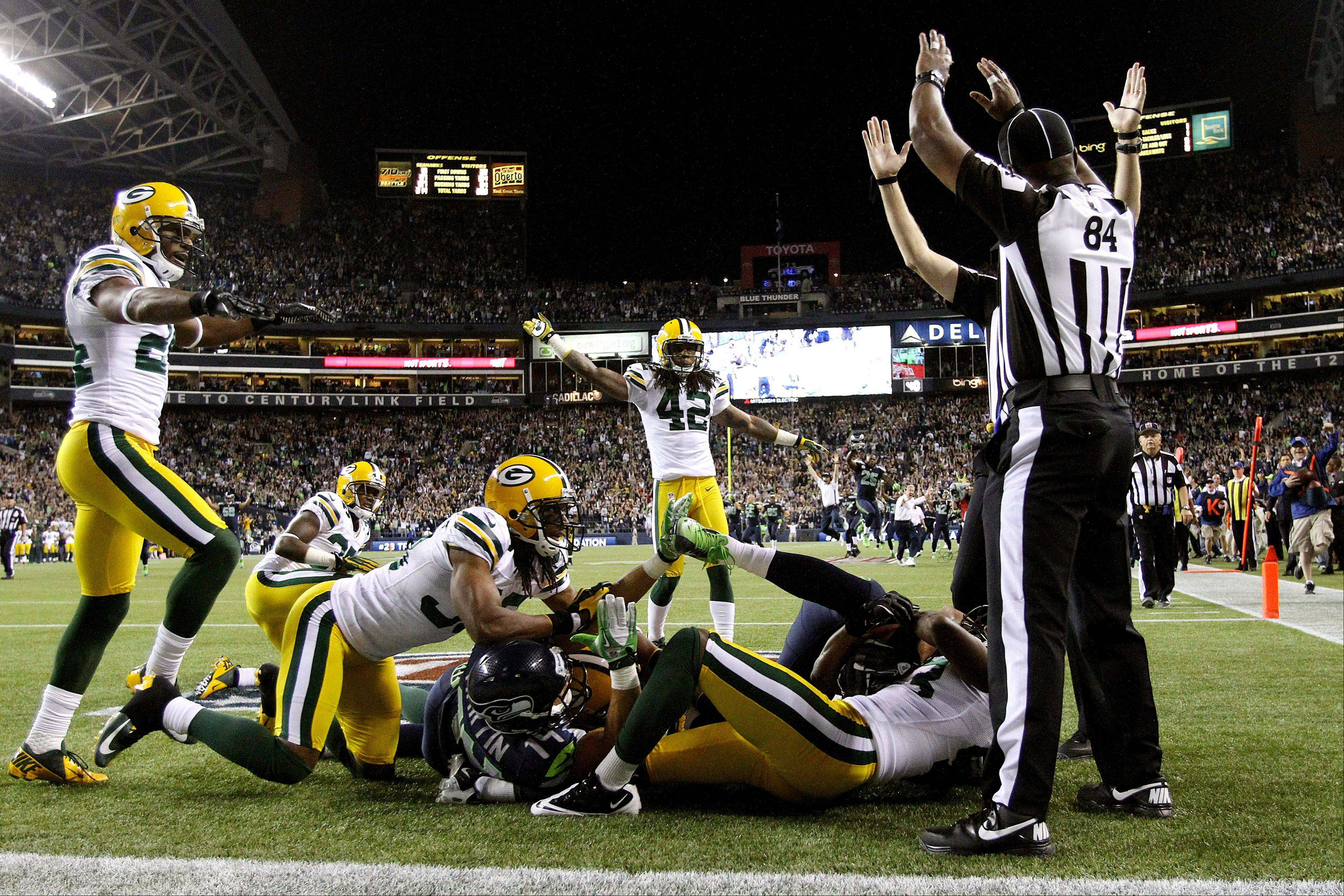 Officials signal after Seattle Seahawks wide receiver Golden Tate pulled in a last-second pass from quarterback Russell Wilson to defeat the Green Bay Packers 14-12 on Monday night in Seattle. The touchdown call stood after review.