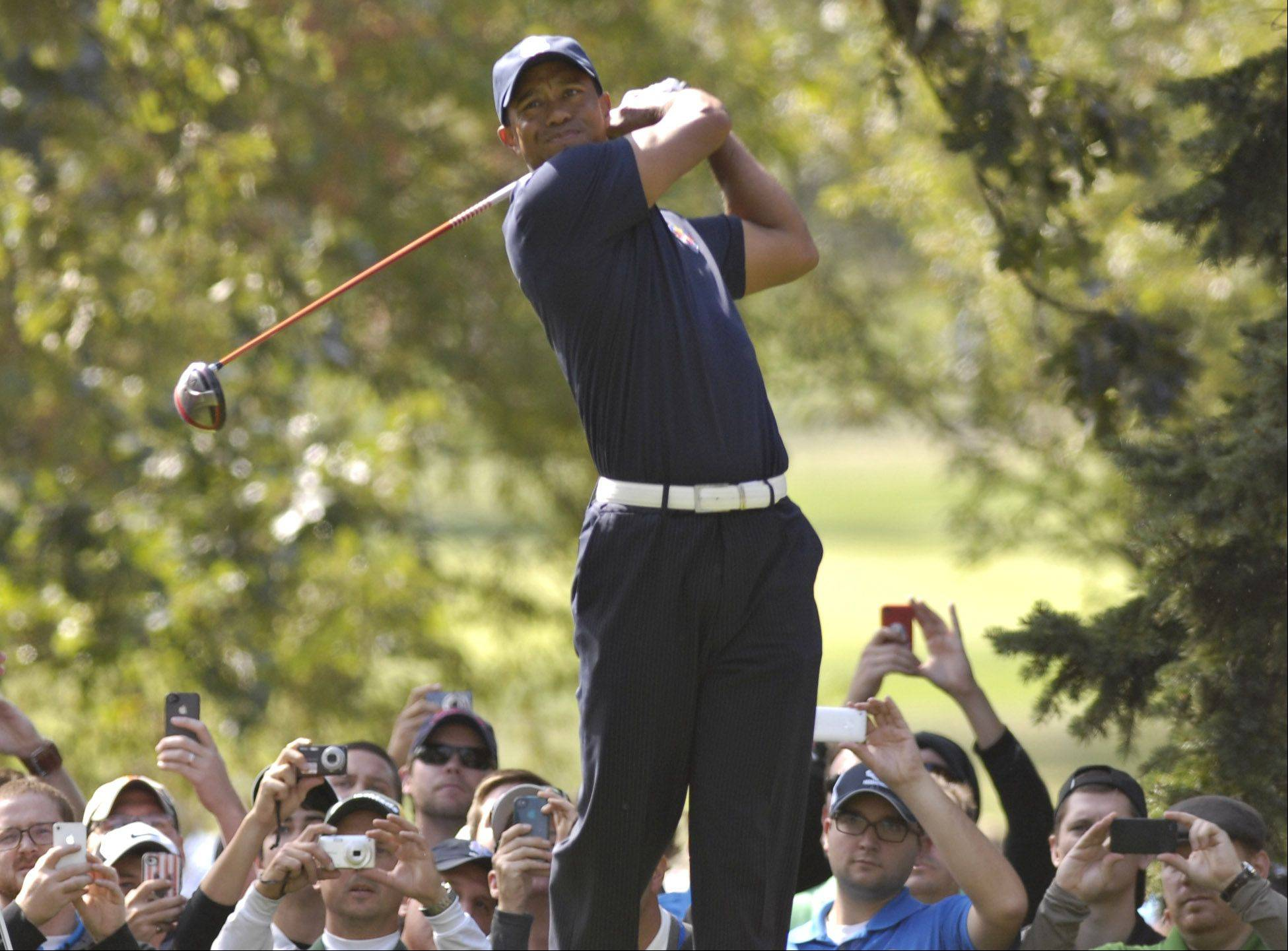 With a sea of camera-toting fans behind him, Tiger Woods watches a tee shot.