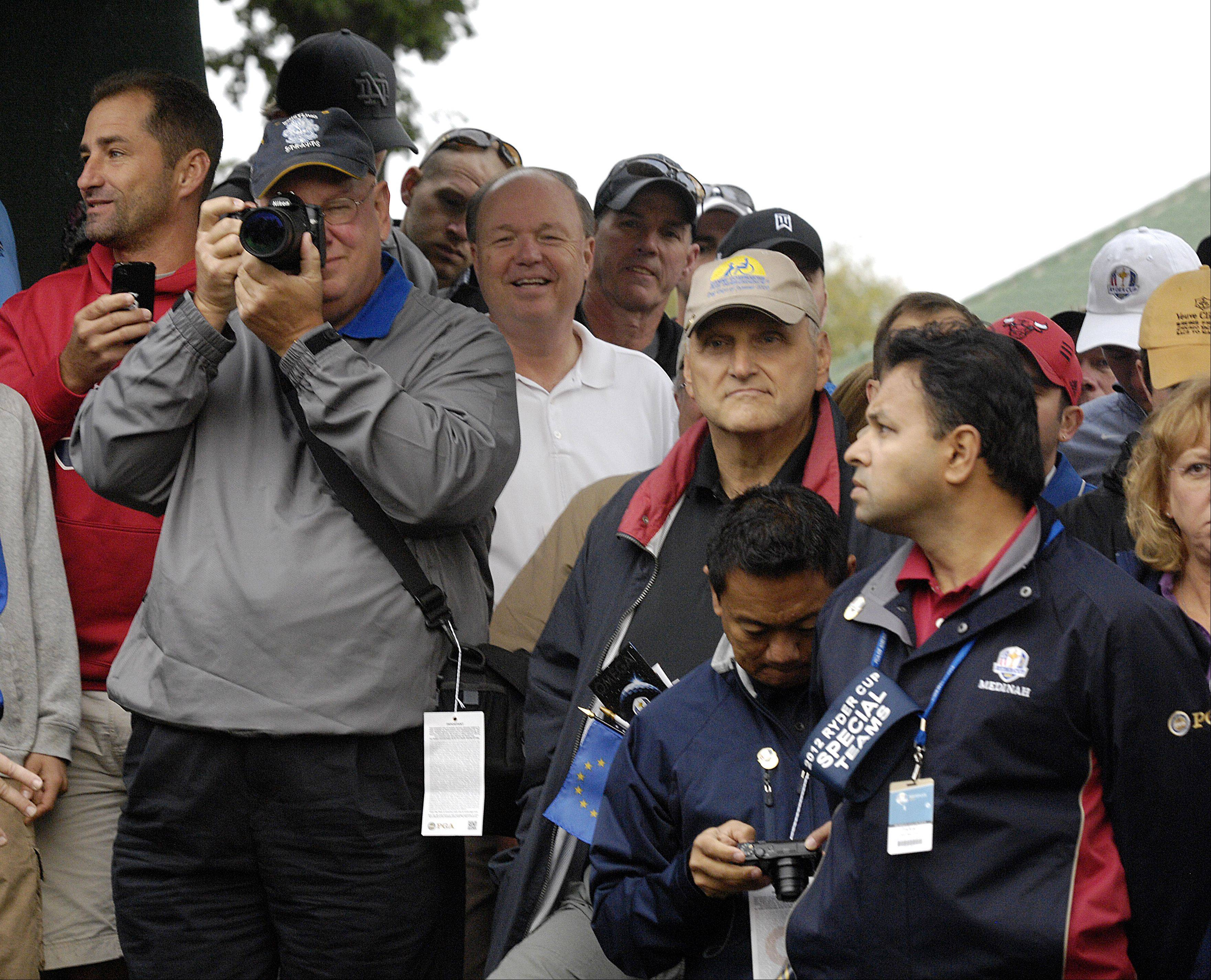 Golf fans try to get a photo and glimpse of the European Ryder Cup team.