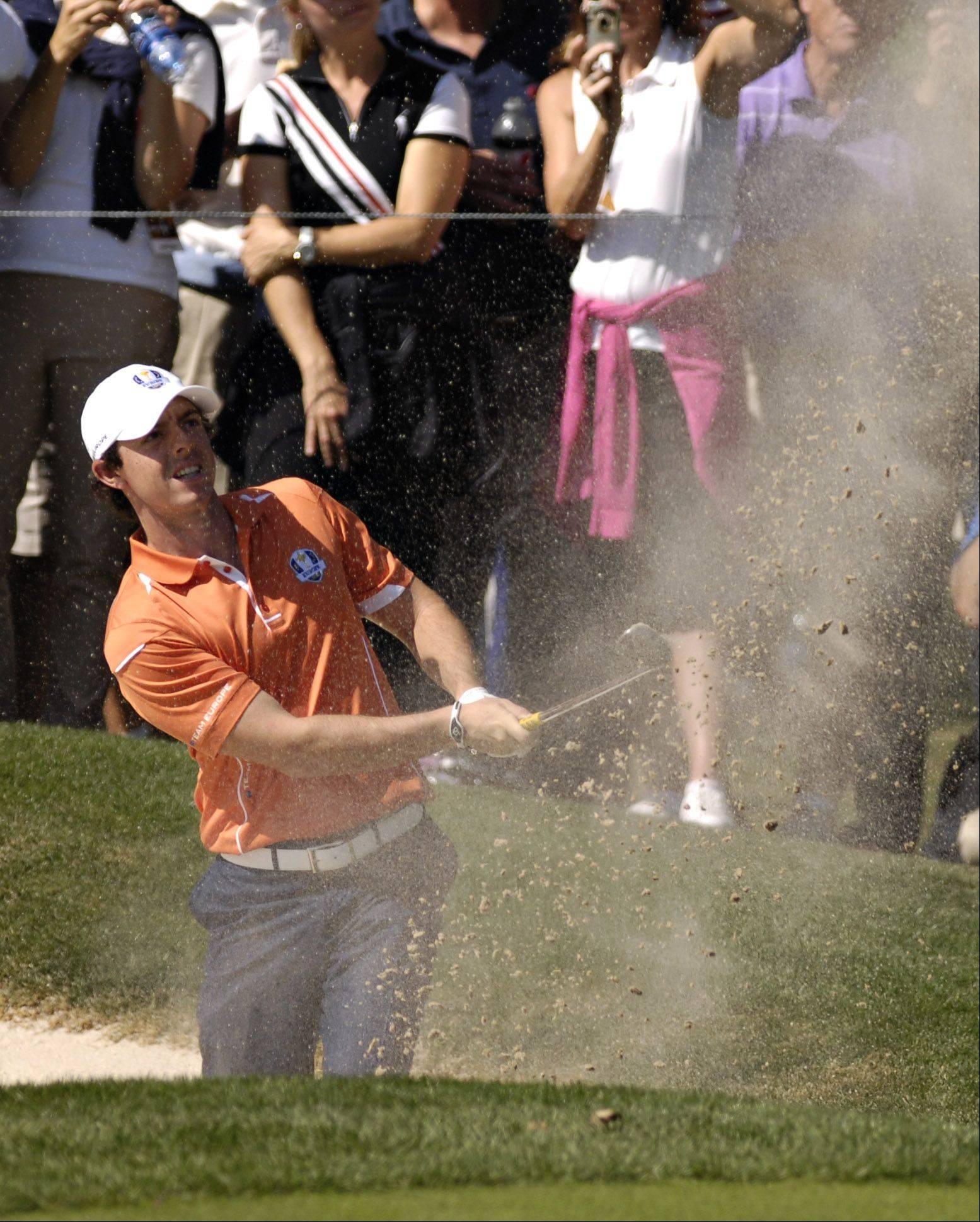 Team Europe's Rory McIlroy blasts out of a bunker.