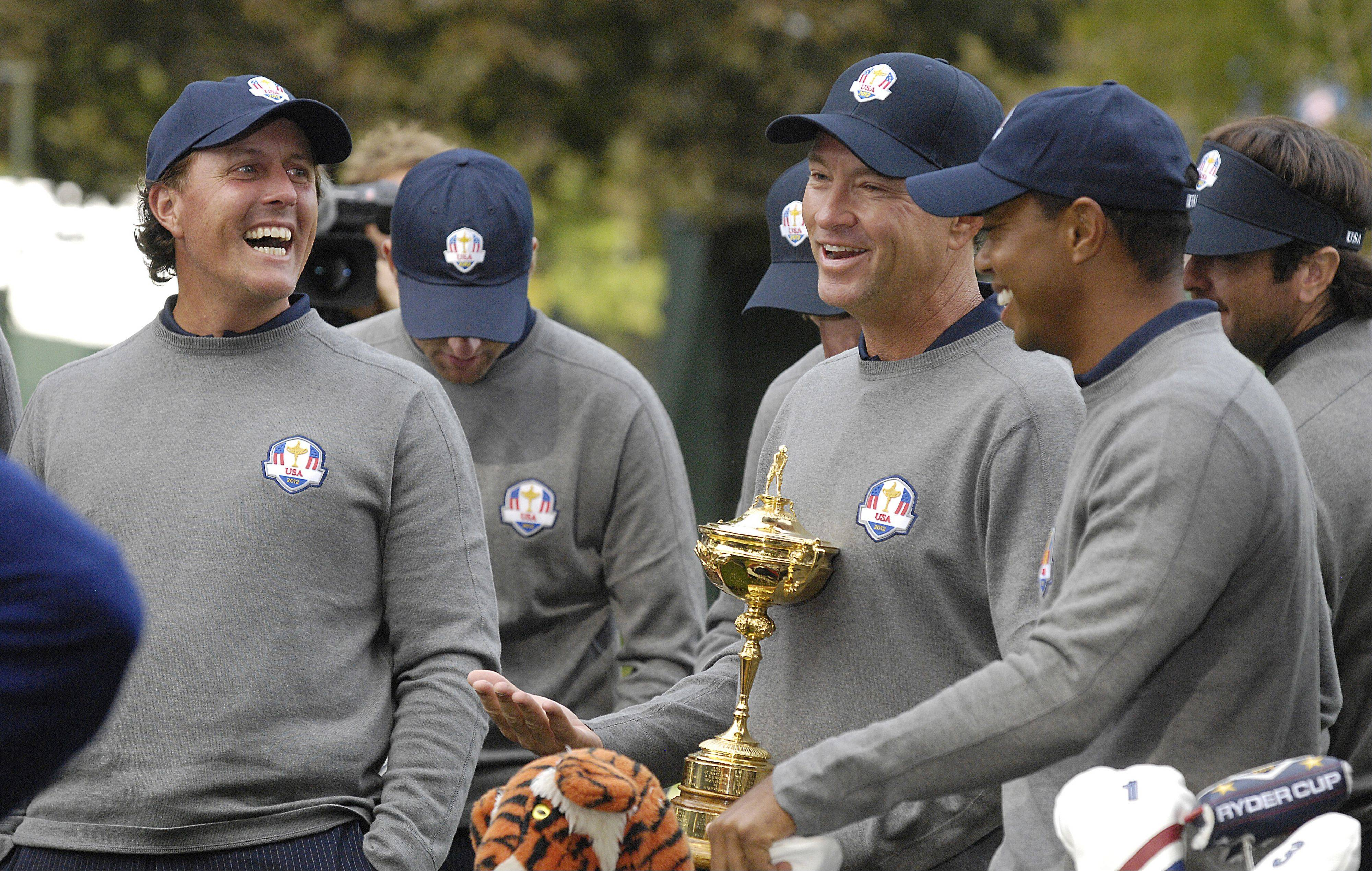 Phil Mickelson, Davis Love III, and Tiger Woods joke around during the U.S. Ryder Cup team photo session.