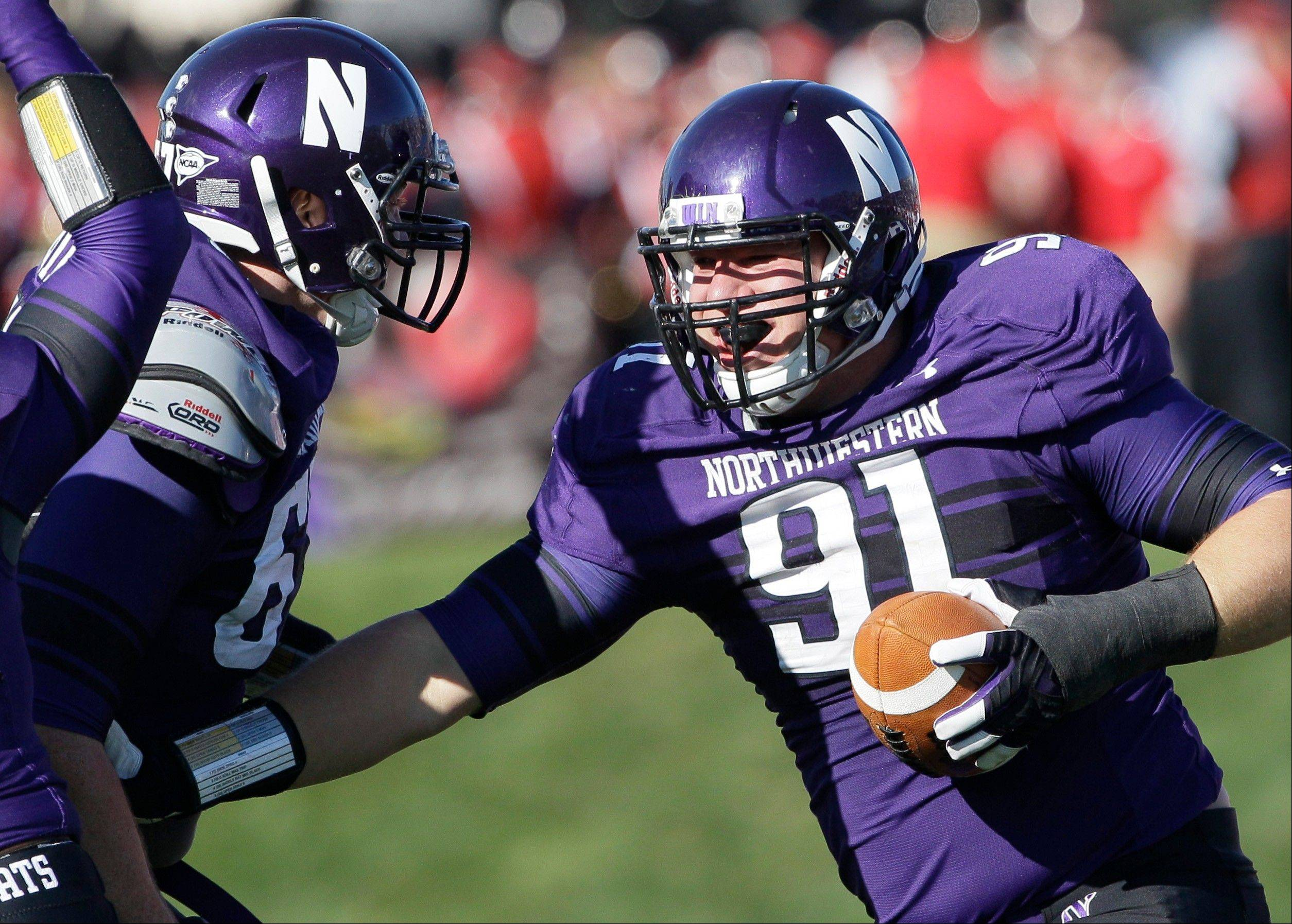 Northwestern defensive line Brian Arnfelt celebrates Saturday with defensive line Sean McEvilly after recovering a fumble against South Dakota in Evanston. Northwestern and Minnesota are two feel-good stories so far this season. Both teams are 4-0.