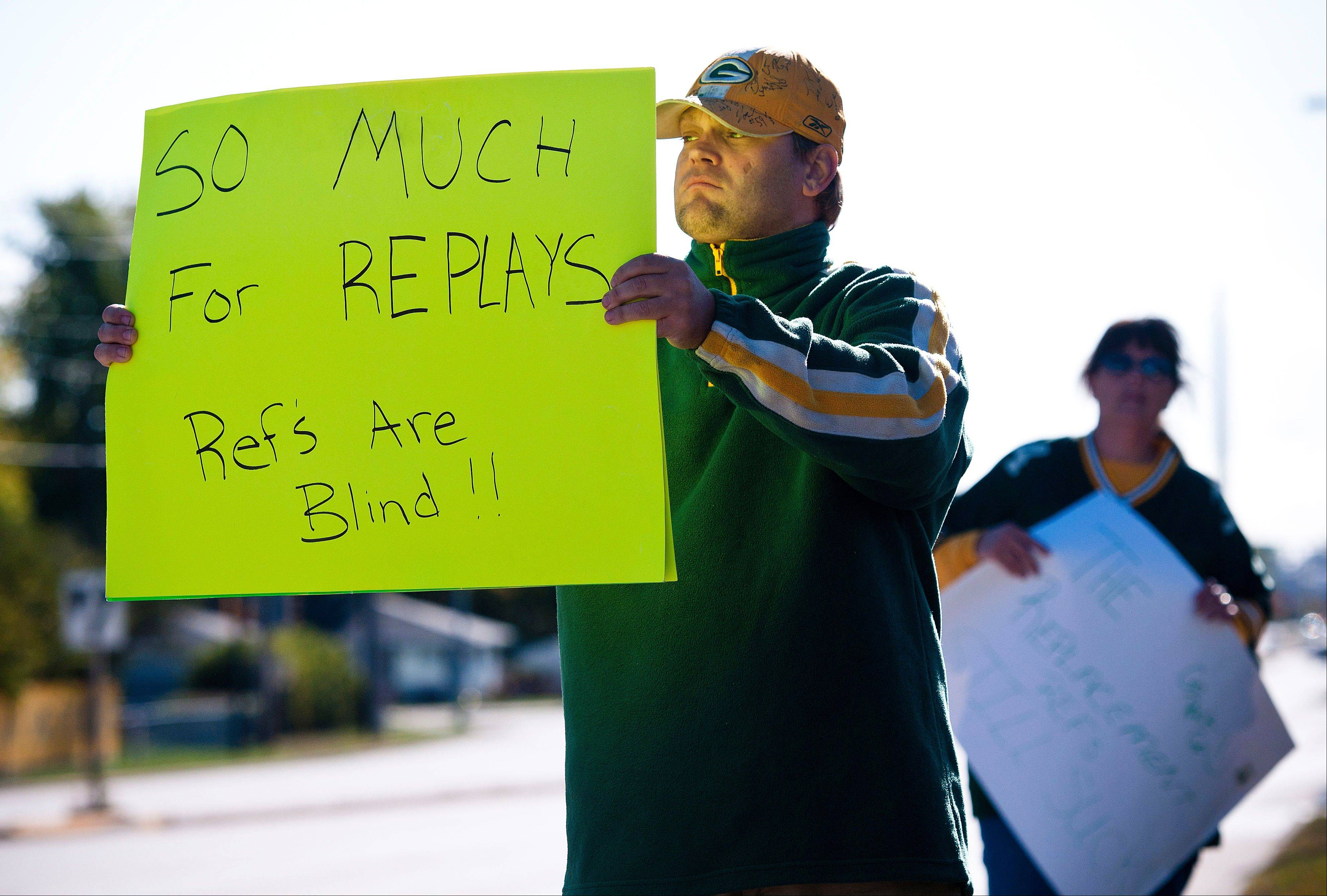 Green Bay Packers fan Mike LePak holds a sign Tuesday on Lombardi Avenue in Green Bay, Wis., in protest of a controversial call in the Packers 14-12 loss to the Seattle Seahawks Monday night in Seattle. Just when it seemed that NFL coaches, players and fans couldn't get any angrier, along came a fiasco that trumped any of the complaints from the weekend.
