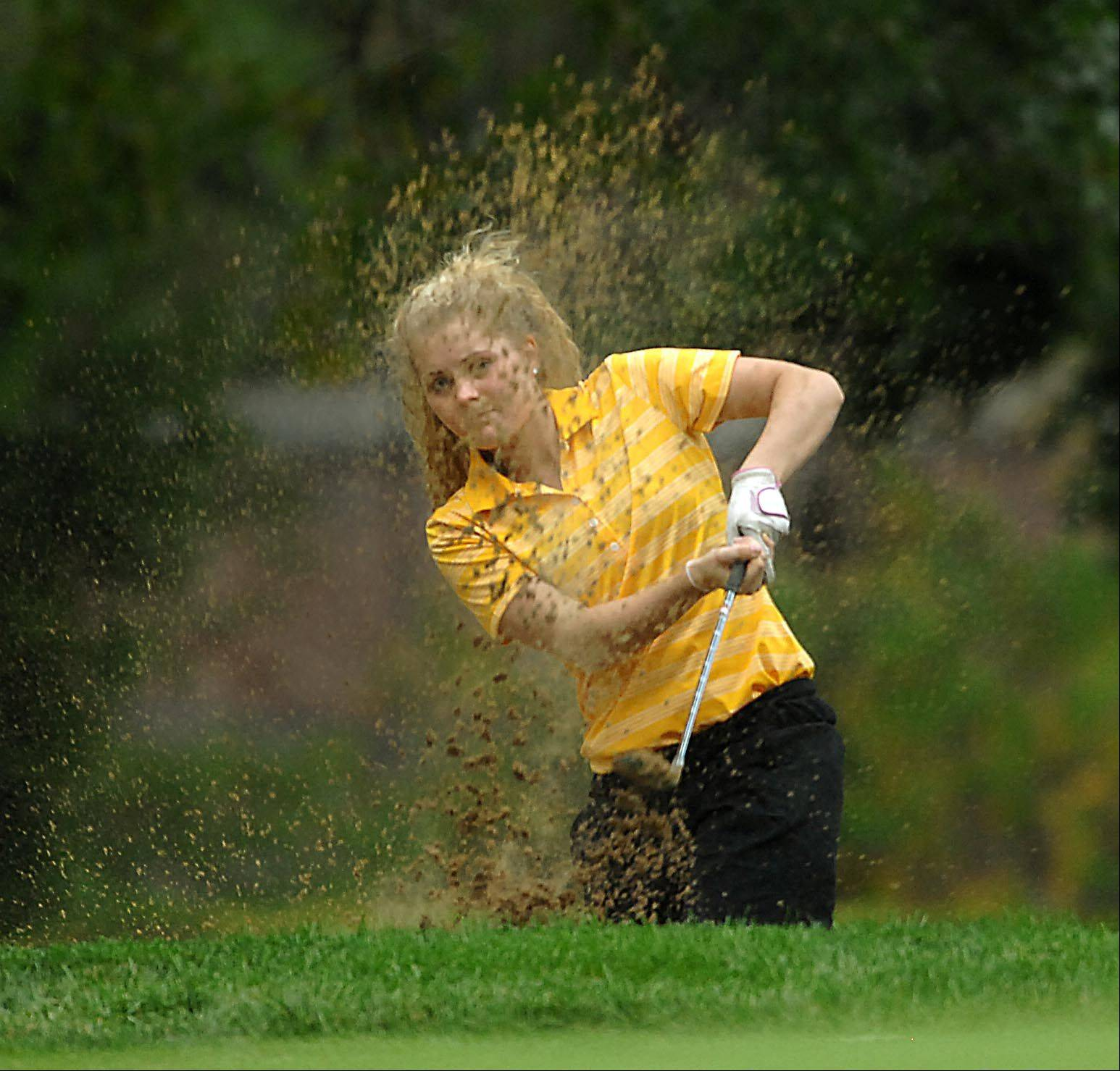 Jacobs's Kaitlyn Woloszyk sprays sand Monday at the Elgin Country Club girls golf invitational.