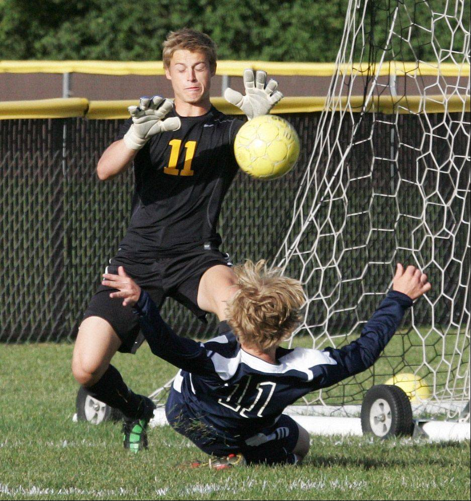 Carmel goalkeeper Michael Zucco blocks a shot by St. Viator's Jackson Owens during Tuesday's soccer game in Mundelein.