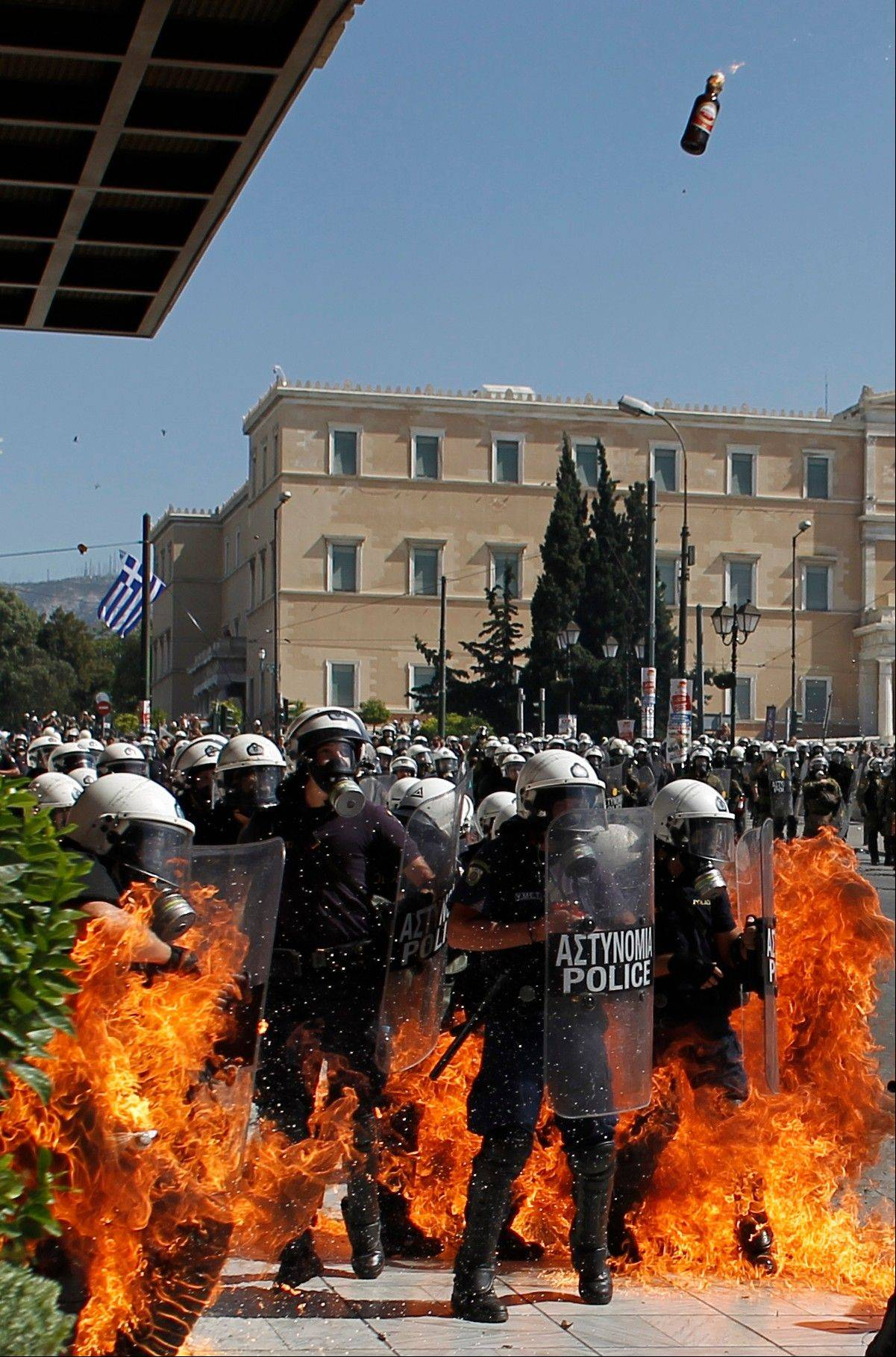 A fire bomb explodes among riot police during clashes in Athens Wednesday. Greek workers walked off the job Wednesday for the first general strike since the country�s coalition government was formed in June, as the prime minister and finance minister hammered out a package of $14.87 billion in spending cuts.