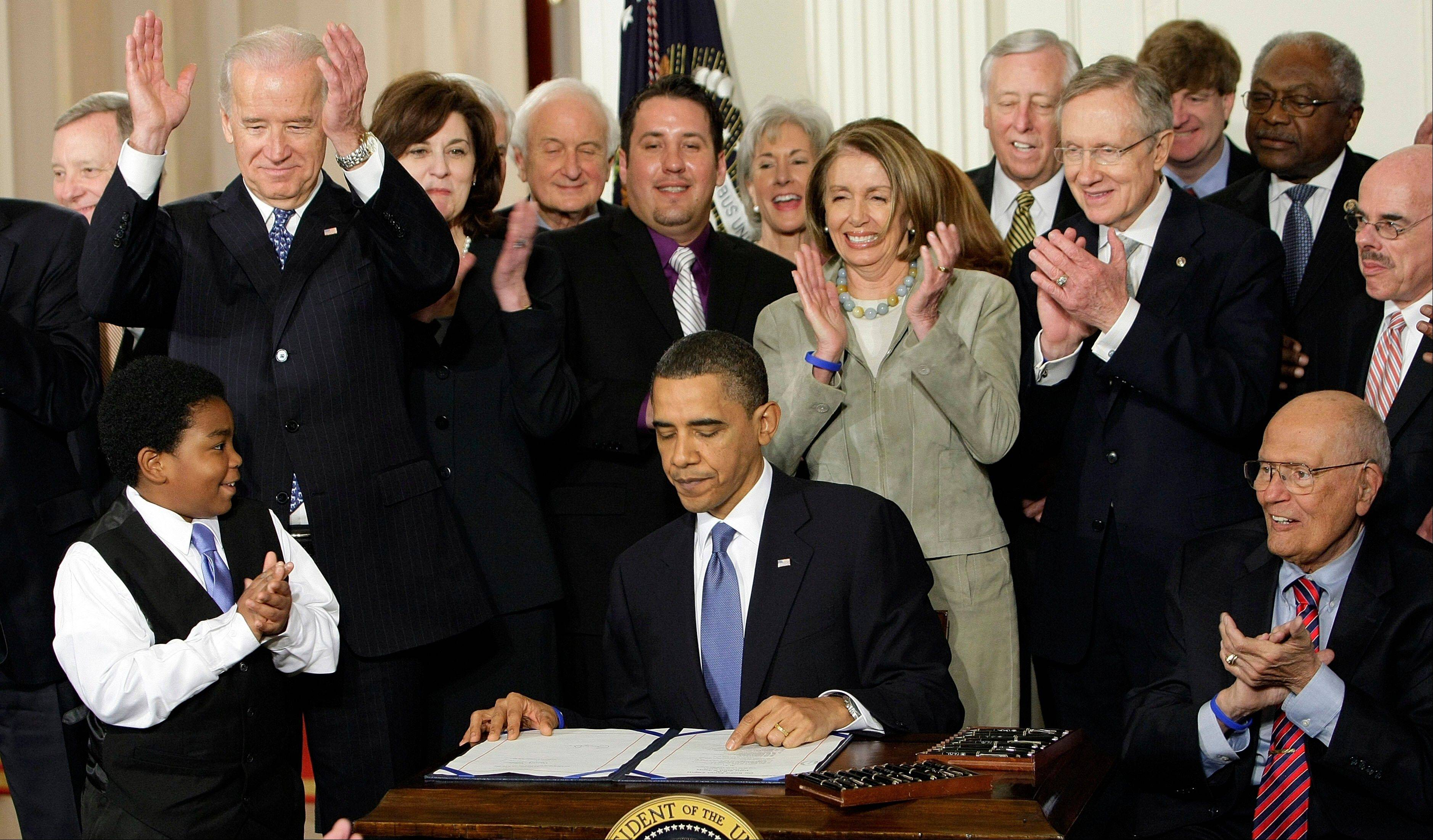 Participants applaud in the East Room of the White House in Washington, Tuesday, March 23, 2010, as President Barack Obama signs the health care bill. Americans may not be all that crazy about President Barack Obama�s health care law, but a new poll shows they don�t see it going away.
