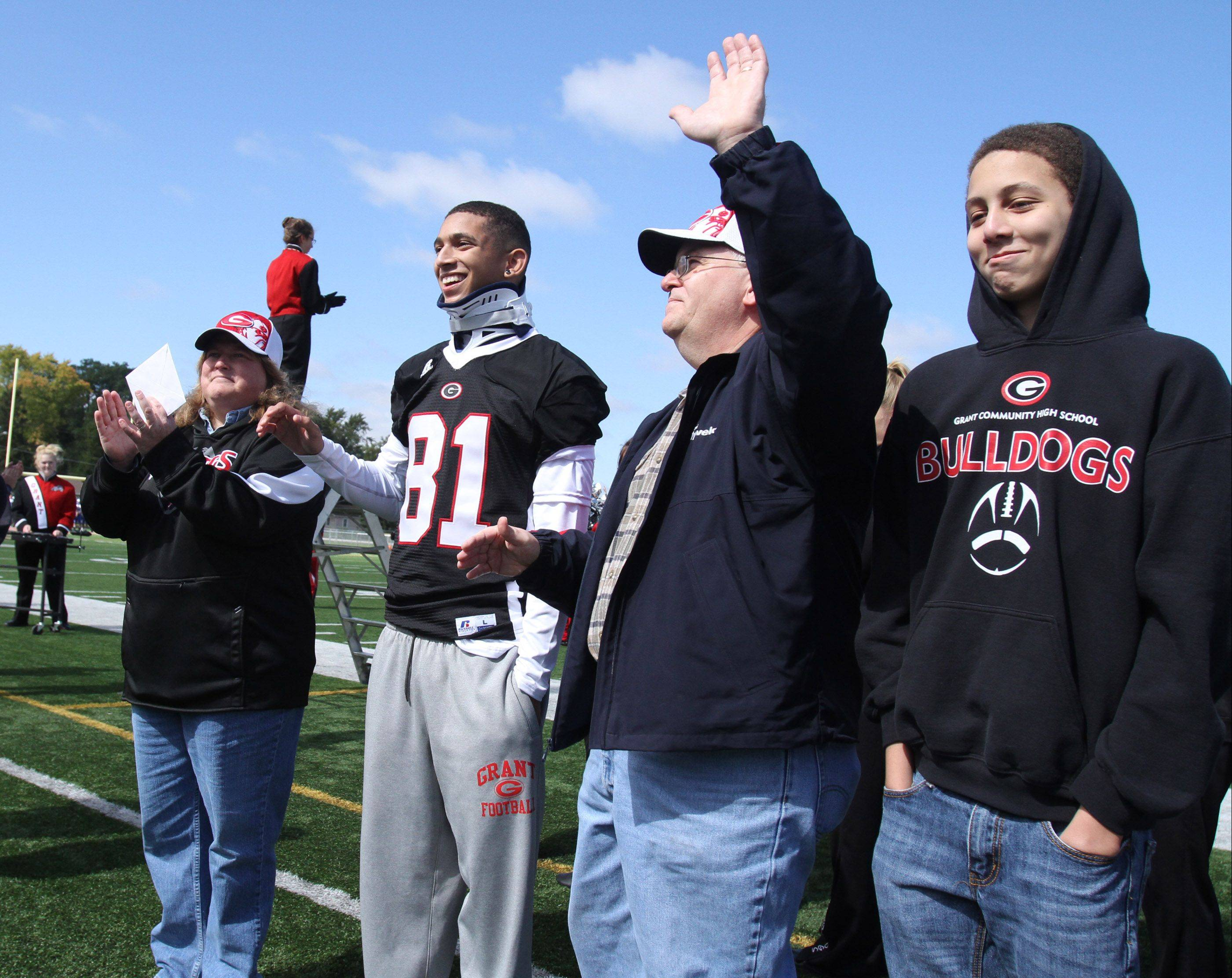 Ray Gomoll waves to Grant fans after his son, injured cornerback Chris Gomoll (81), received a check before the school's homecoming game against Vernon Hills on Saturday. At left is Chris's mother, Angie, and brother Ethan, 13, right.