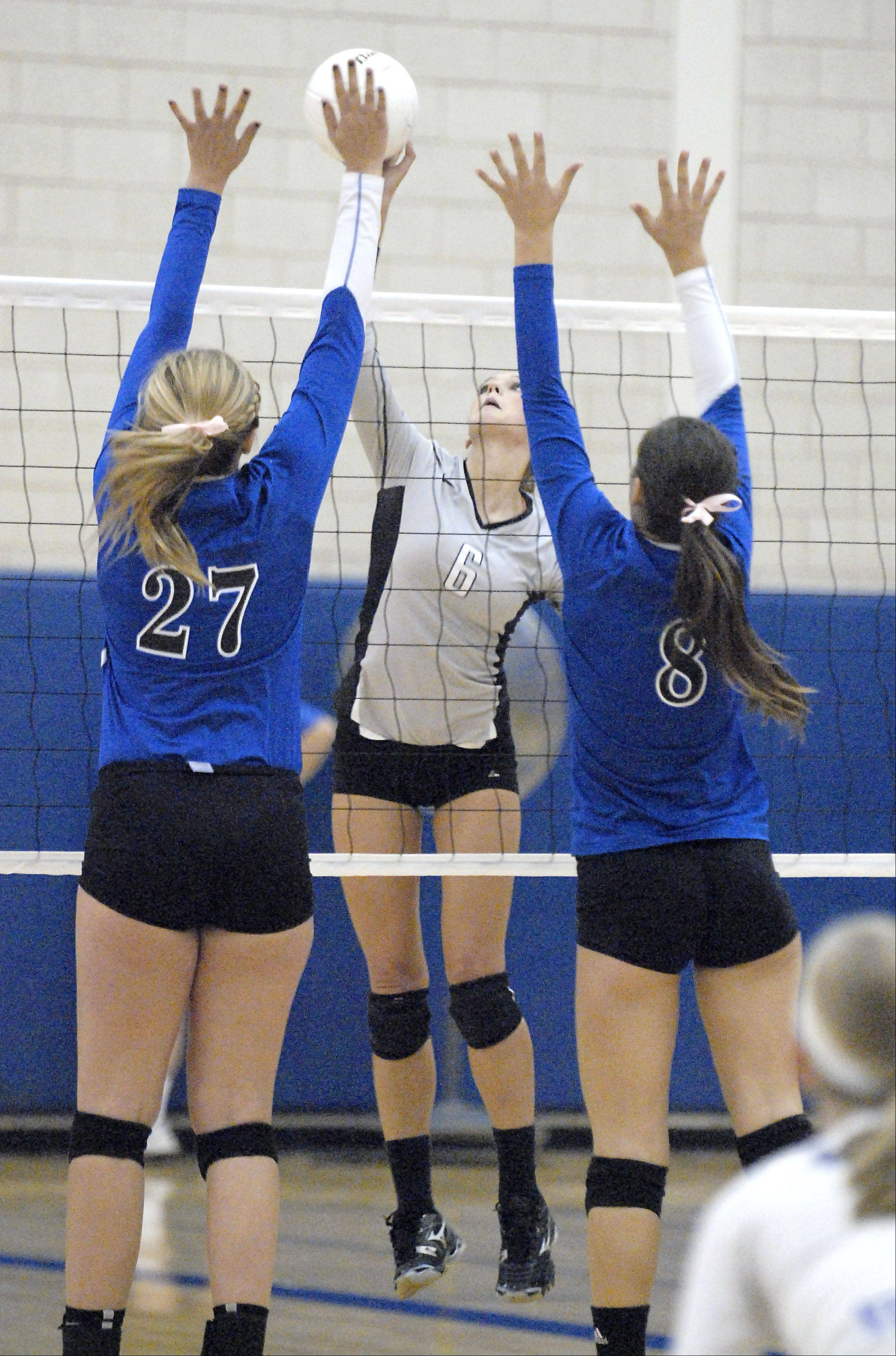 Kaneland�s Lyndi Scholl spikes the ball over to Geneva�s Taylor Marmitt and Jess Wicinski in the third match on Wednesday, September 26.