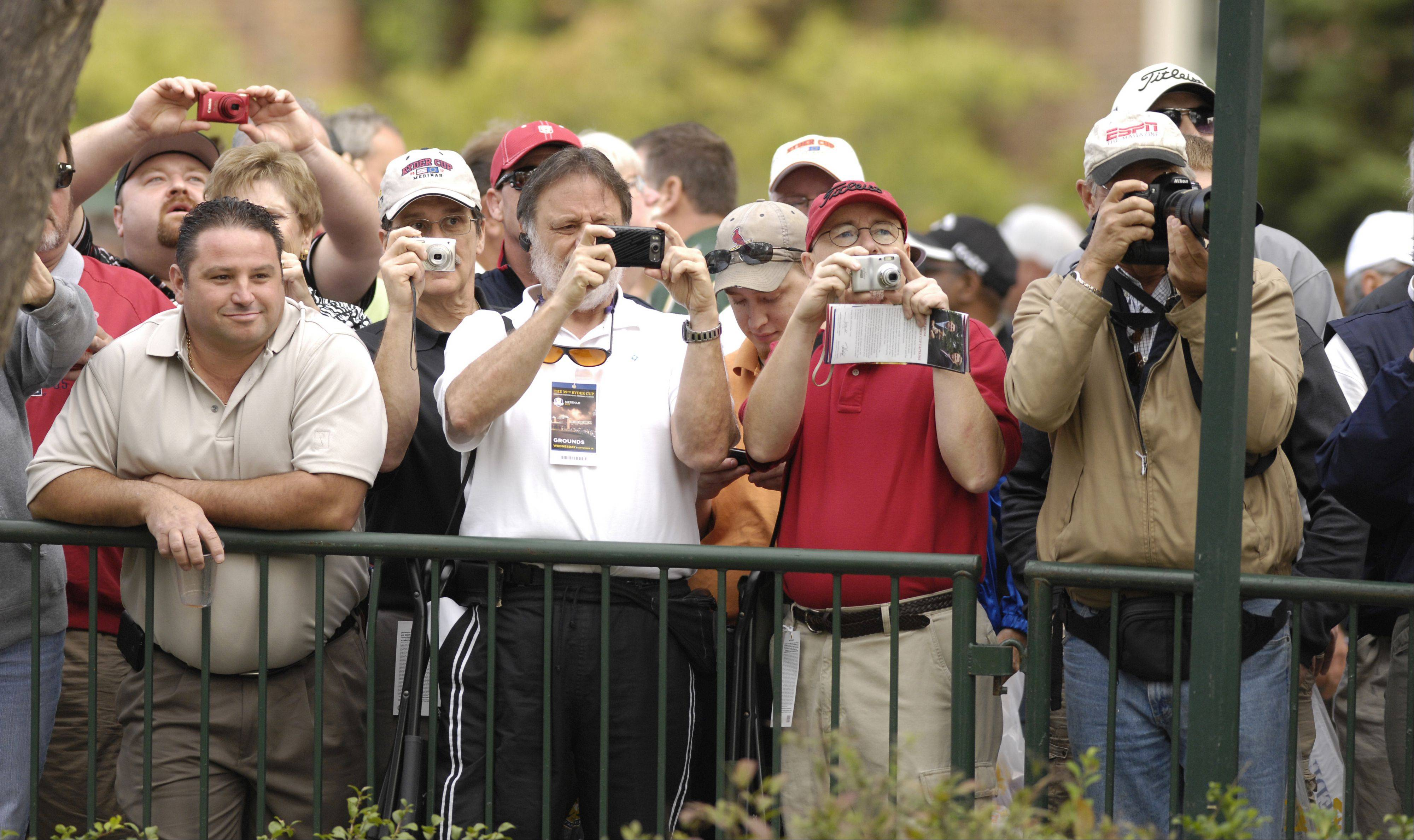 Fans attempt to get a photograph of Team United States players as they leave the first tee during a Ryder Cup practice round Wednesday.