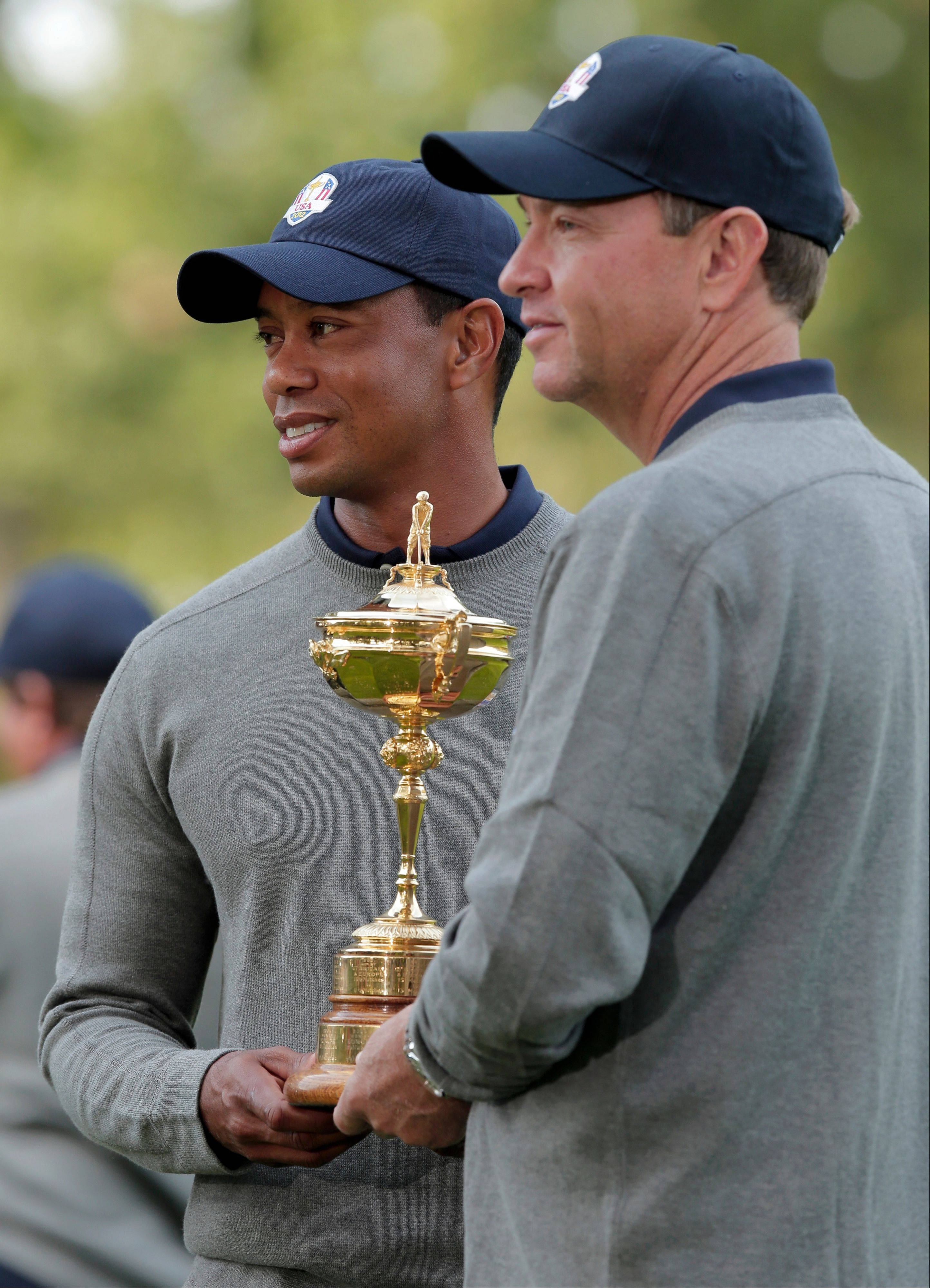 USA's captain Davis Love III and Tiger Woods pose with the Ryder Cup trophy at Medinah Country Club.