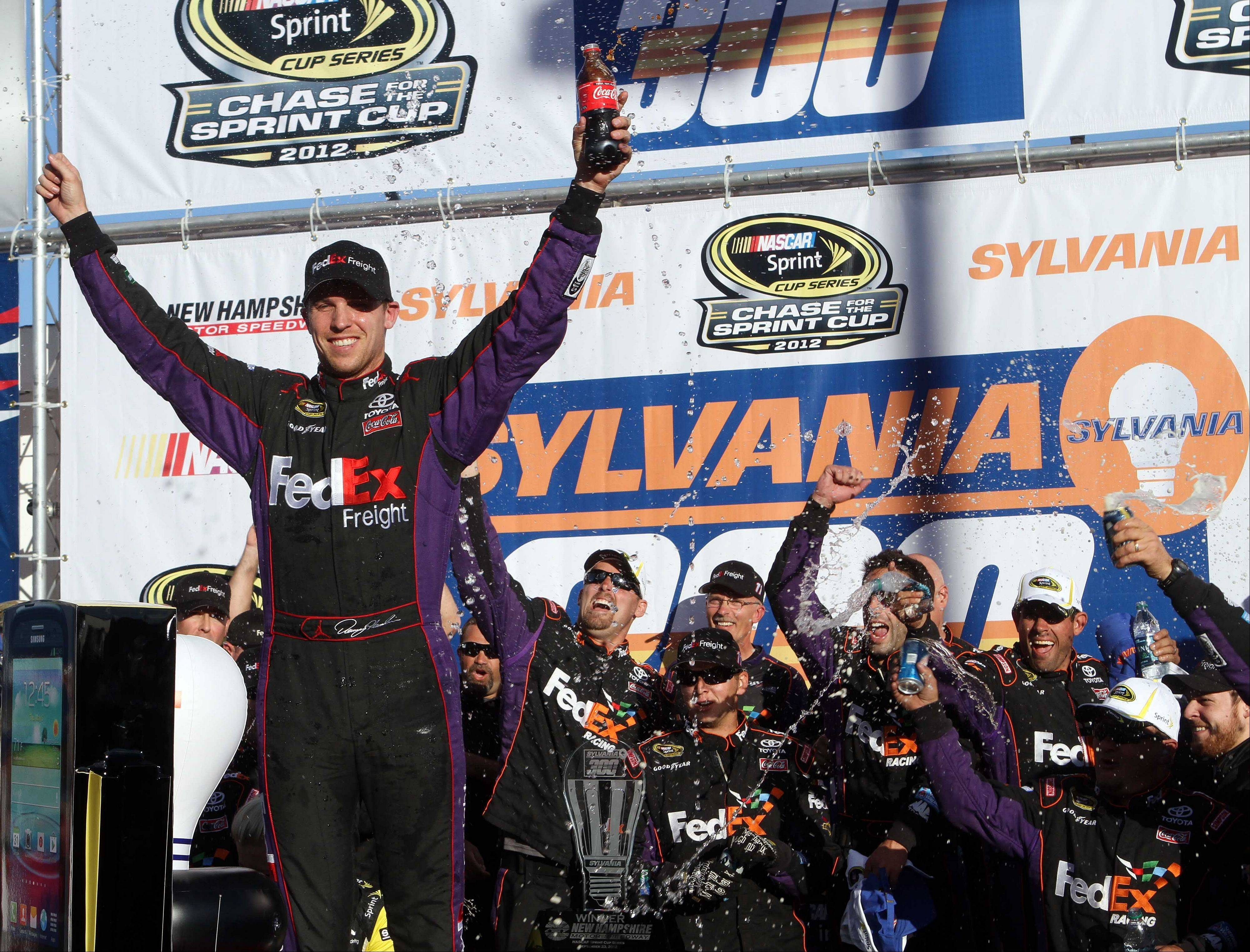 NASCAR driver Denny Hamlin celebrates Sunday with his team after winning the NASCAR Sprint Cup Series auto race at New Hampshire Motor Speedway.