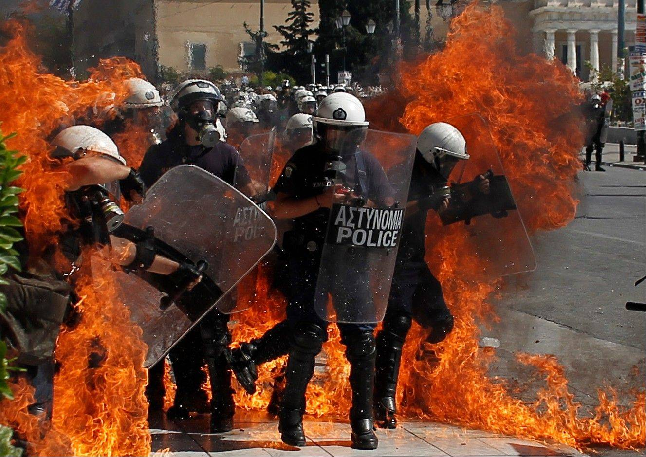 A fire bomb explodes among riot police during clashes in Athens Wednesday Sept. 26, 2012. Greek workers walked off the job Wednesday for the first general strike since the country's coalition government was formed in June, as the prime minister and finance minister hammered out a package of euros 11.5 billion ($14.87 billion) in spending cuts.