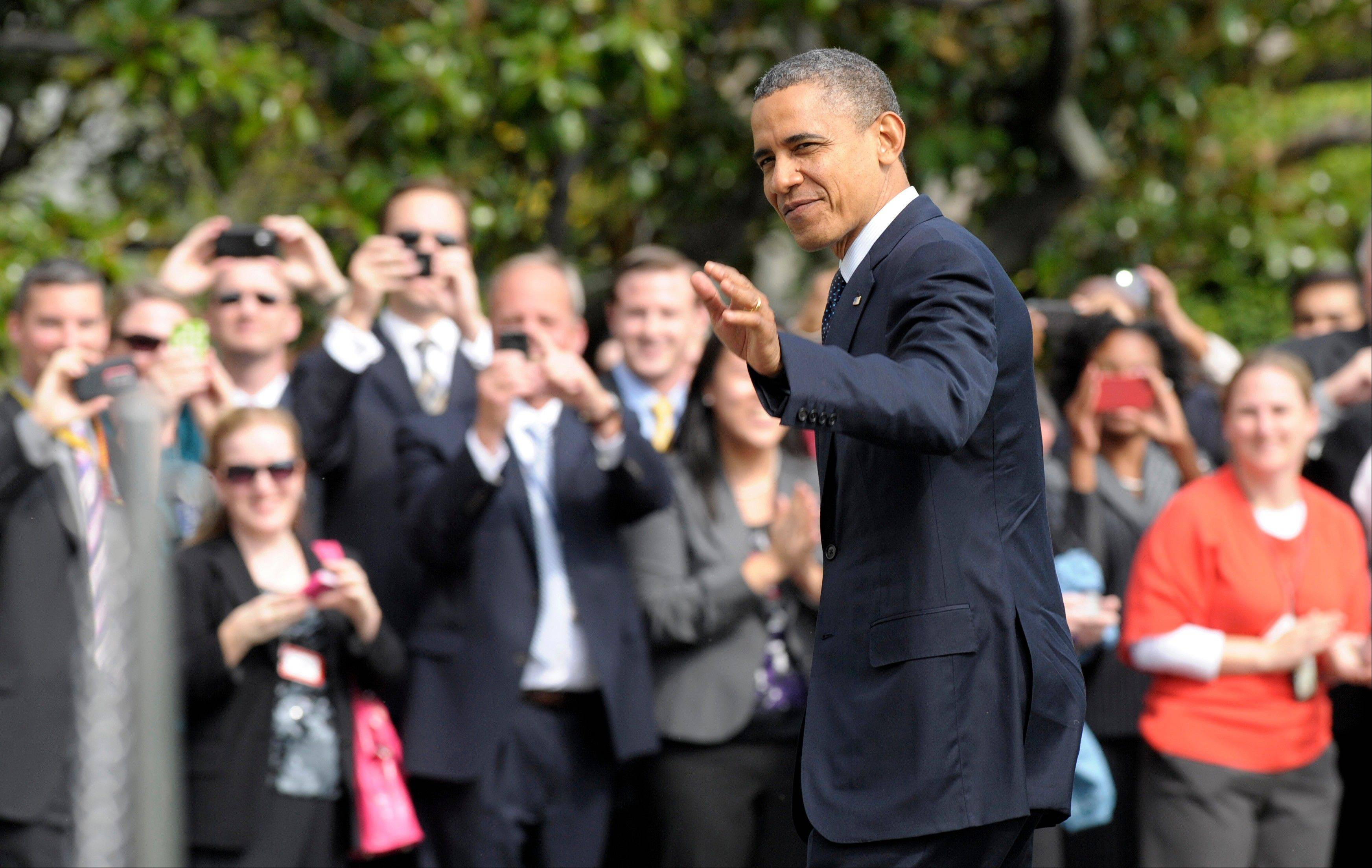 President Barack Obama waves as he returns to the the White House in Washington, Tuesday.