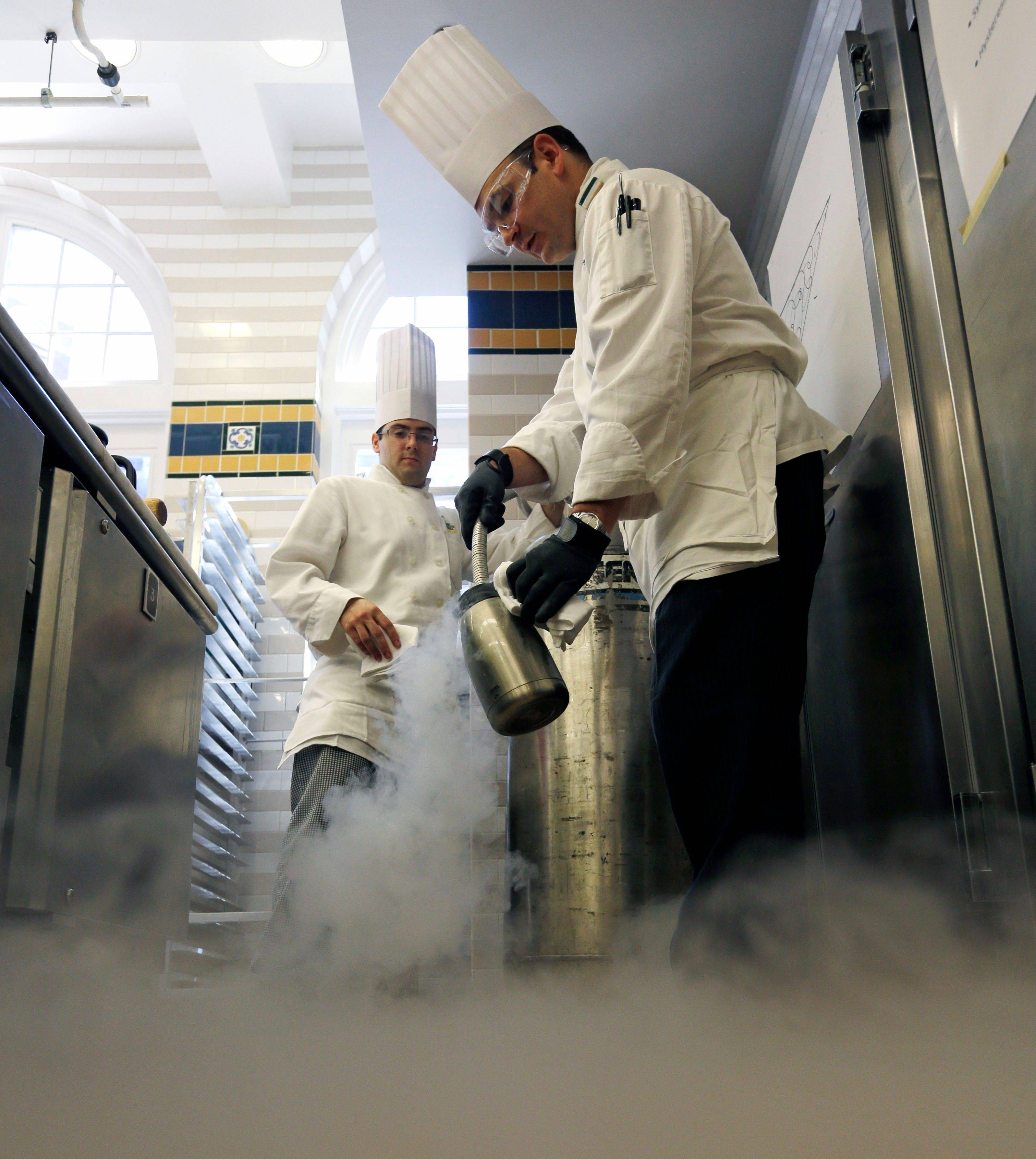 Culinary Institute of America instructor chef Francisco Migoya, right, fills a container with liquid nitrogen as pastry manager-in-training Douglas Phillips looks on in one of the kitchen classrooms at the esteemed New York cooking school.