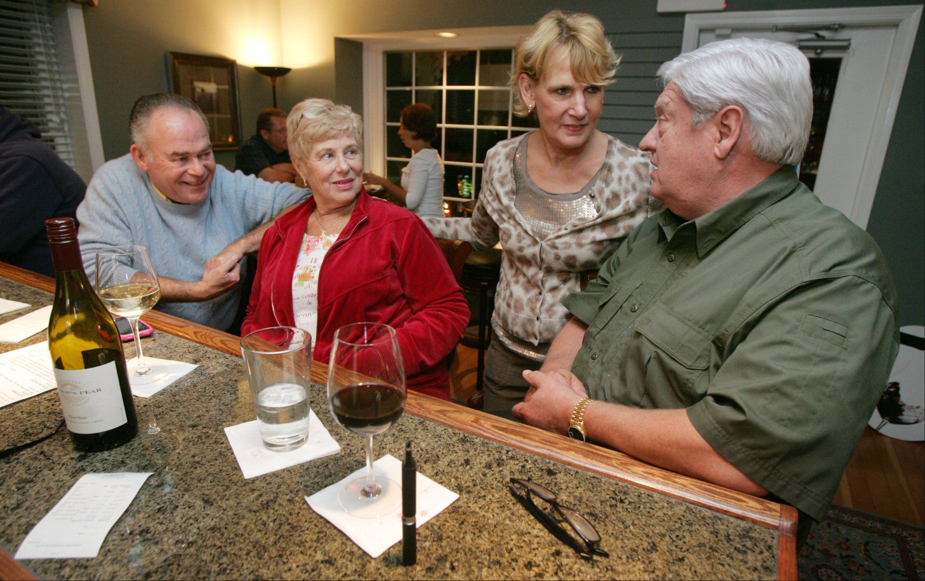 Bard Boand of North Barrington, right, talks to server Kathy Cramer while he and his friends Mary Schick and Will Askew enjoy some wine at WineSplash in Long Grove.
