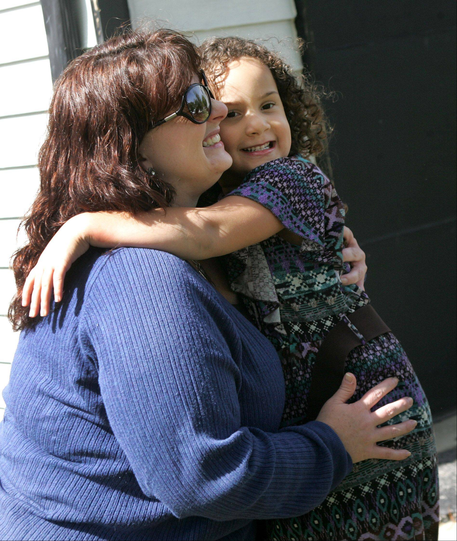 Diana Jensen of Aurora hugs her daughter, Livia, 4, Wednesday before the two met the Aurora 911 operator who responded to Livia's call and dispatched assistance to their home. Livia called 911 because Jensen, who has Lupus, suddenly felt intense pain and was unable to speak.