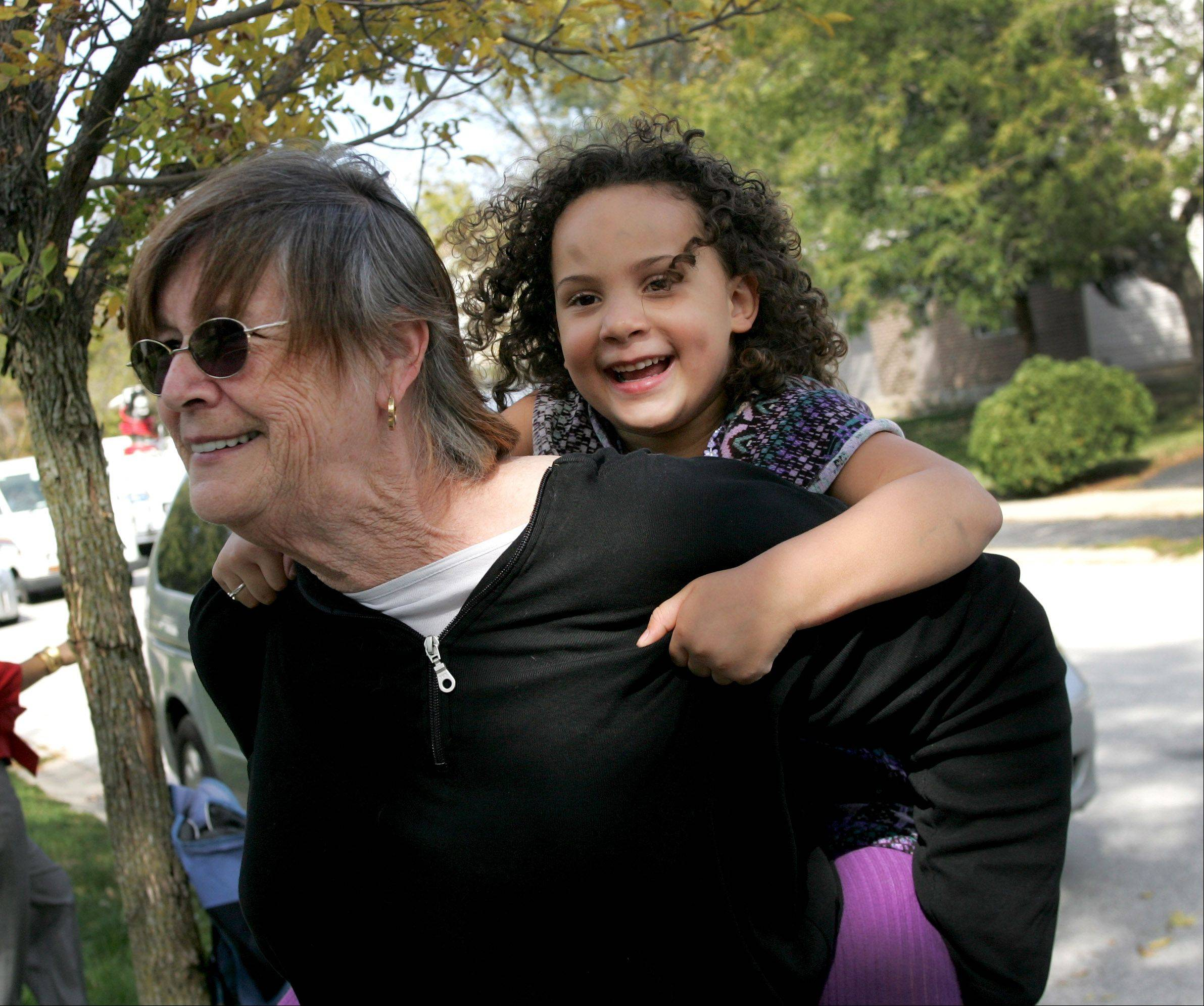 "Livia Jensen, 4, gets a piggyback ride from her mother's friend, Dorothy Anderson of Naperville, whom Livia calls ""Grandma."" Livia helped get medical care for her mother, Diana Jensen, by calling 911 Sunday when family friends like Anderson were not available."