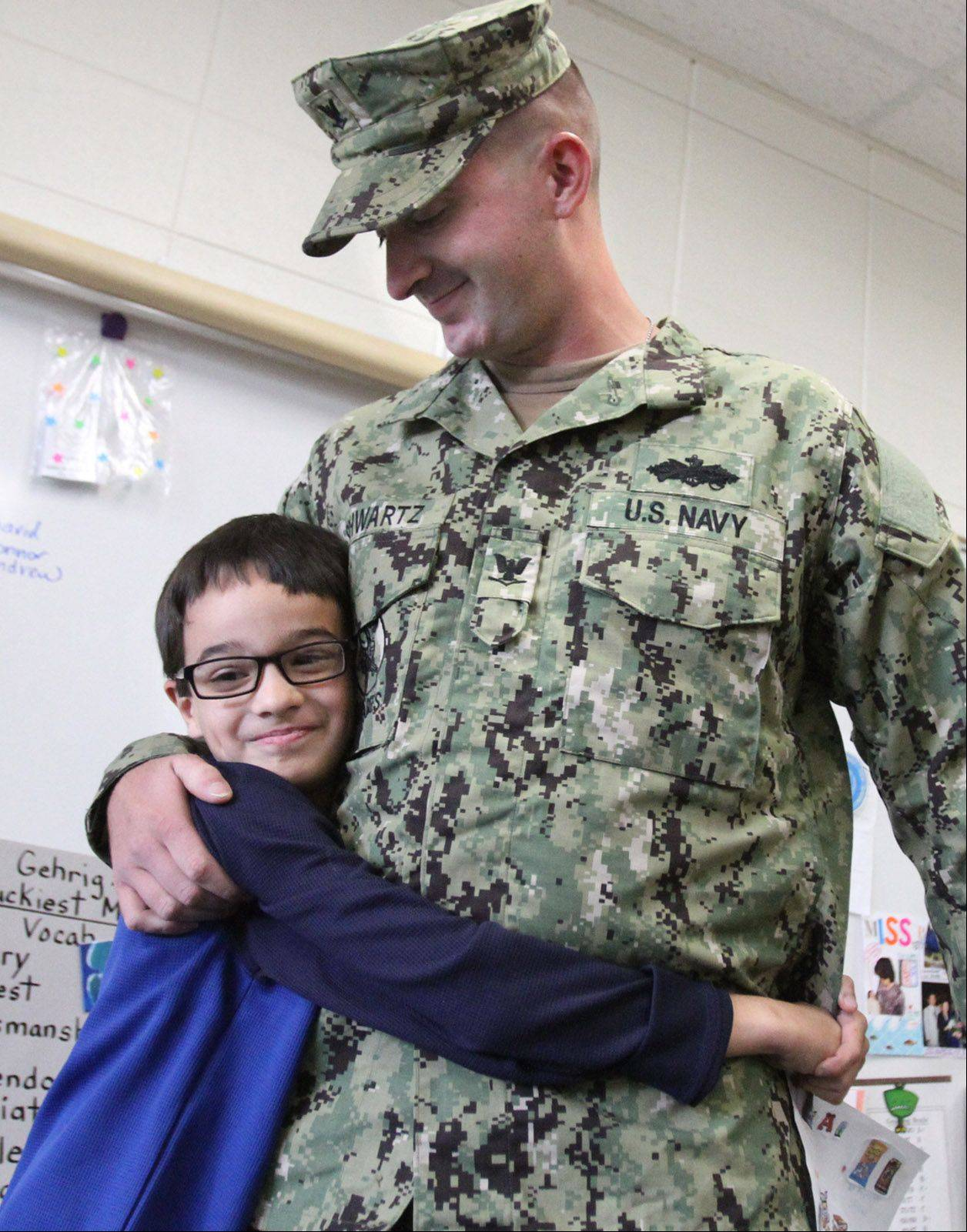 Petty Officer 3rd Class Cameron Schwartz of the U.S. Navy, who was deployed in Afghanistan for eight months, surprises younger brother Julian Trujillo during his fourth-grade class Wednesday at Hunting Ridge School in Palatine.