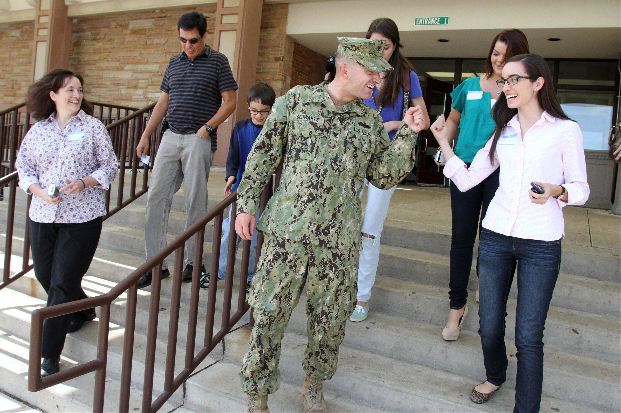 Petty Officer 3rd Class Cameron Schwartz of the U.S. Navy gets a fist bump from younger sister, Haley, as his family leaves Fremd High School in Palatine. Recently back from a deployment in Afghanistan, he visited Fremd and Hunting Ridge School on Wednesday to surprise his siblings.