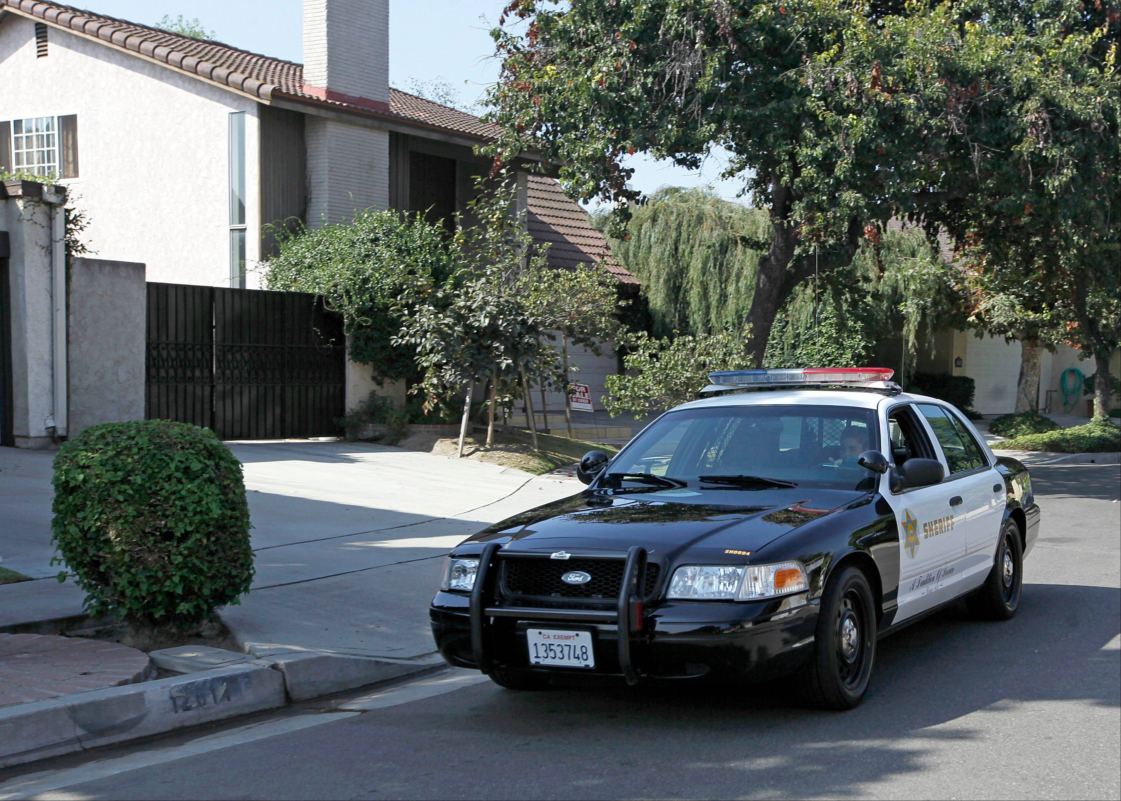 "A Los Angeles County Serriff's deputy in a patrol car passes the home of Nakoula Basseley Nakoula, the man who made the film ""Innocence of Muslims"" that has sparked violent protests, on a street in Cerritos, Calif., Tuesday, Sept. 25, 2012. The filmmaker has received death threats and was forced into hiding, putting his house up for sale, after the 14-minute movie trailer rose to prominence."