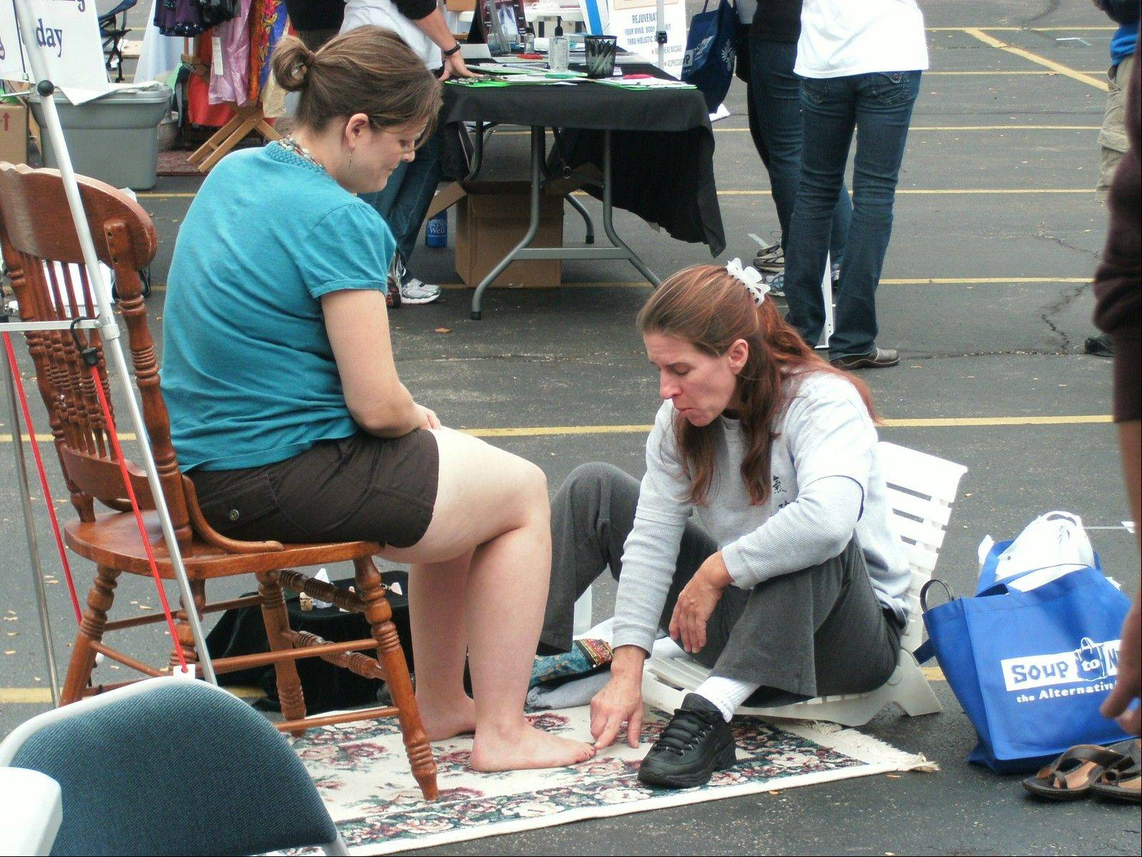 "Darla Tegtmaier performs a ""toe reading"" for Jennifer DuBose at a previous Fox Valley Holistic Health Celebration."