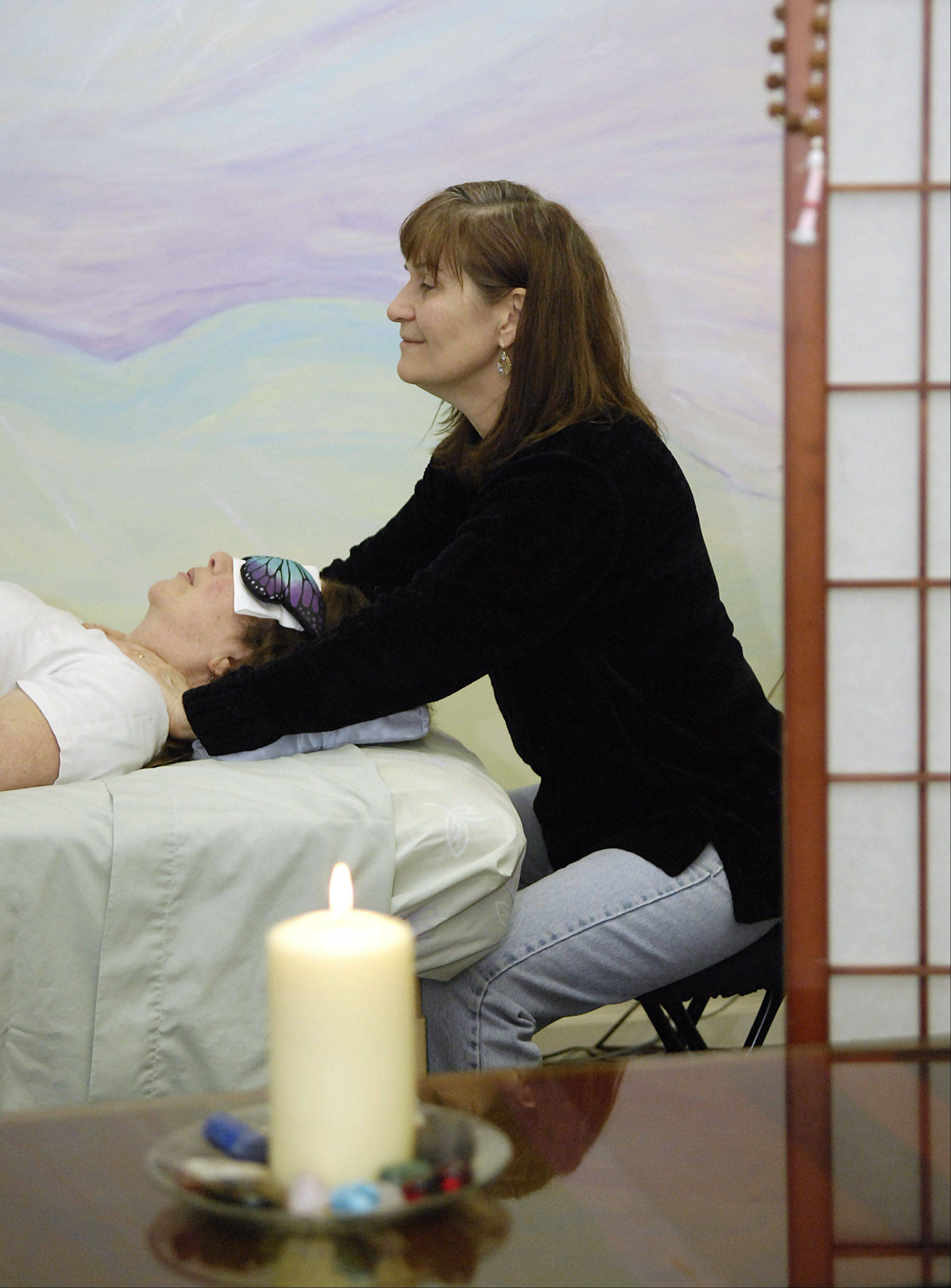 J.R. Carmany, co-owner of Soup to Nuts Alternative Grocery, does a Reiki demonstration. Reiki will be demonstrated at Sunday's Holistic Health Celebration at 716 W. State St., Geneva.