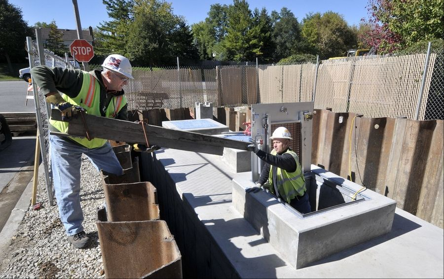 DuPage Water Commission contractors Kevin Sweeney, right, and Wally Callahan are building a water metering station in eastern Naperville, one of several capital projects the financially troubled agency is undertaking.
