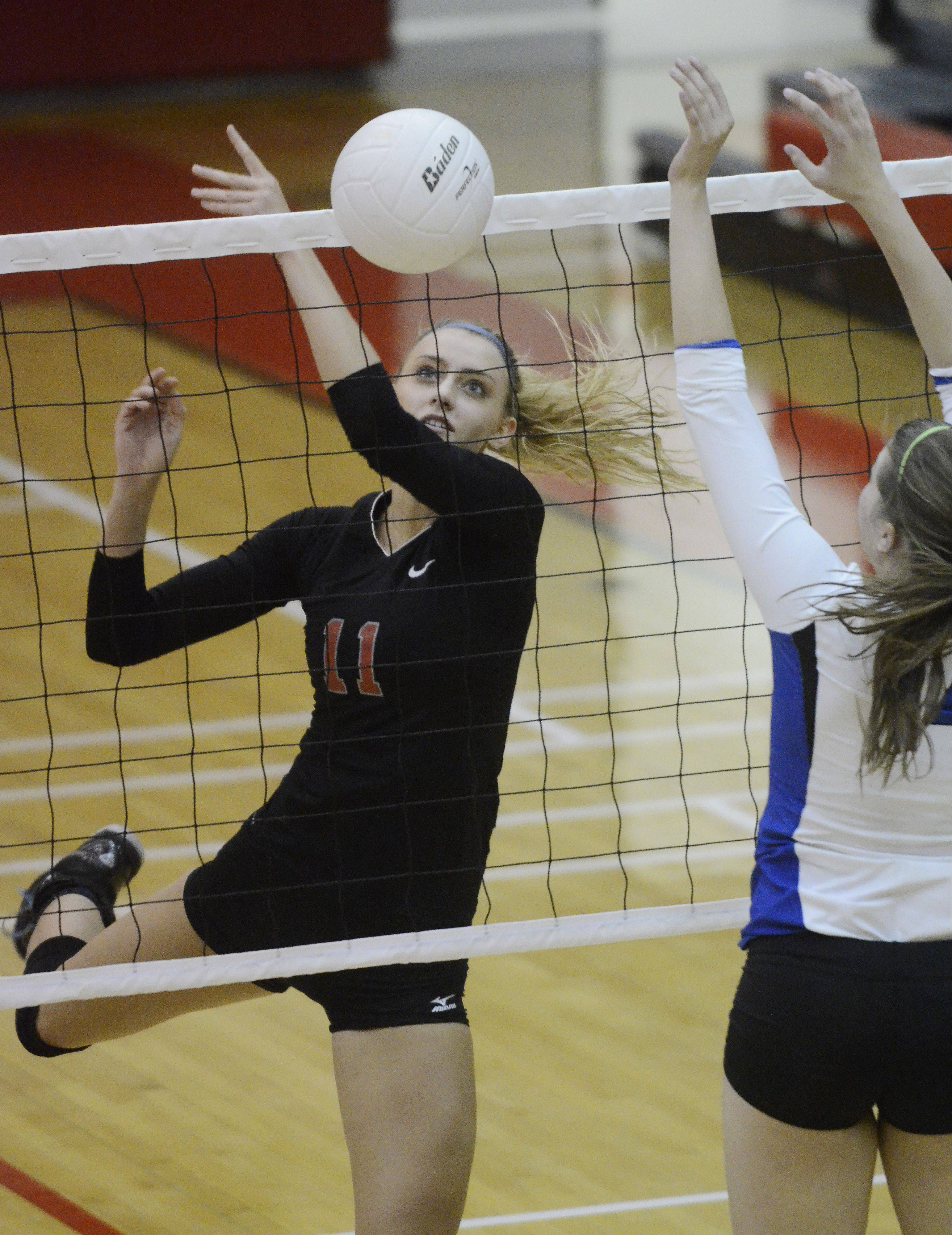 Palatine's Taylor Fricano, left, tries to tip the ball over the net as Lake Zurich's Sydney Glover attempts to block it.