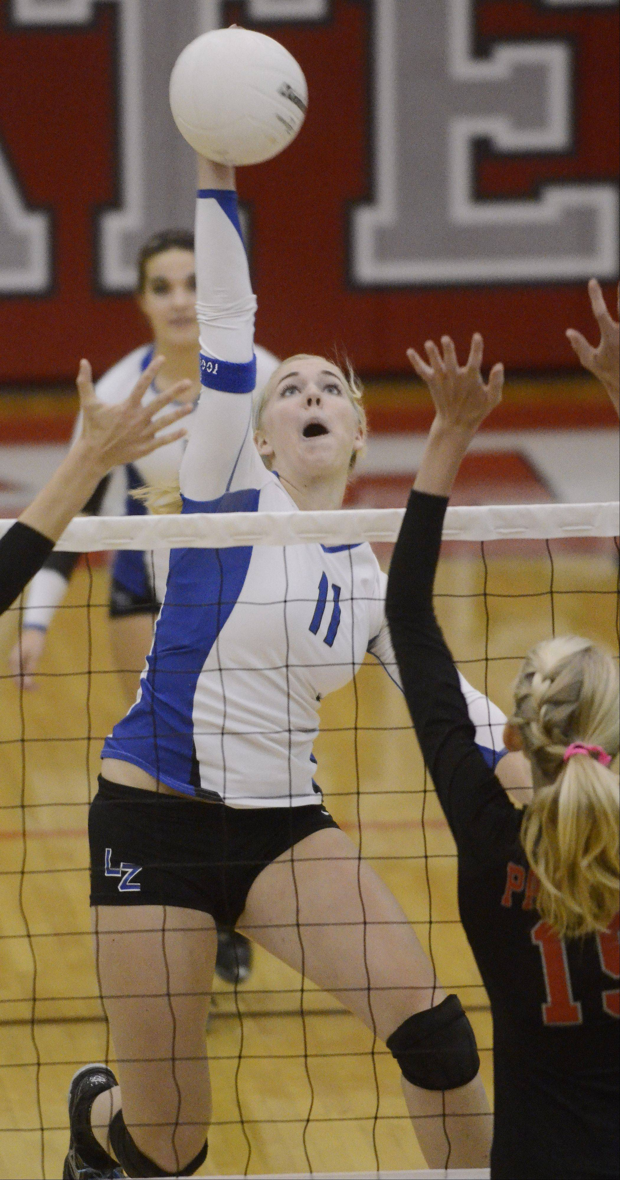 Lake Zurich's Layne Self reaches up for a kill as Palatine's Kim Butler, right, tries to block the ball at the net.