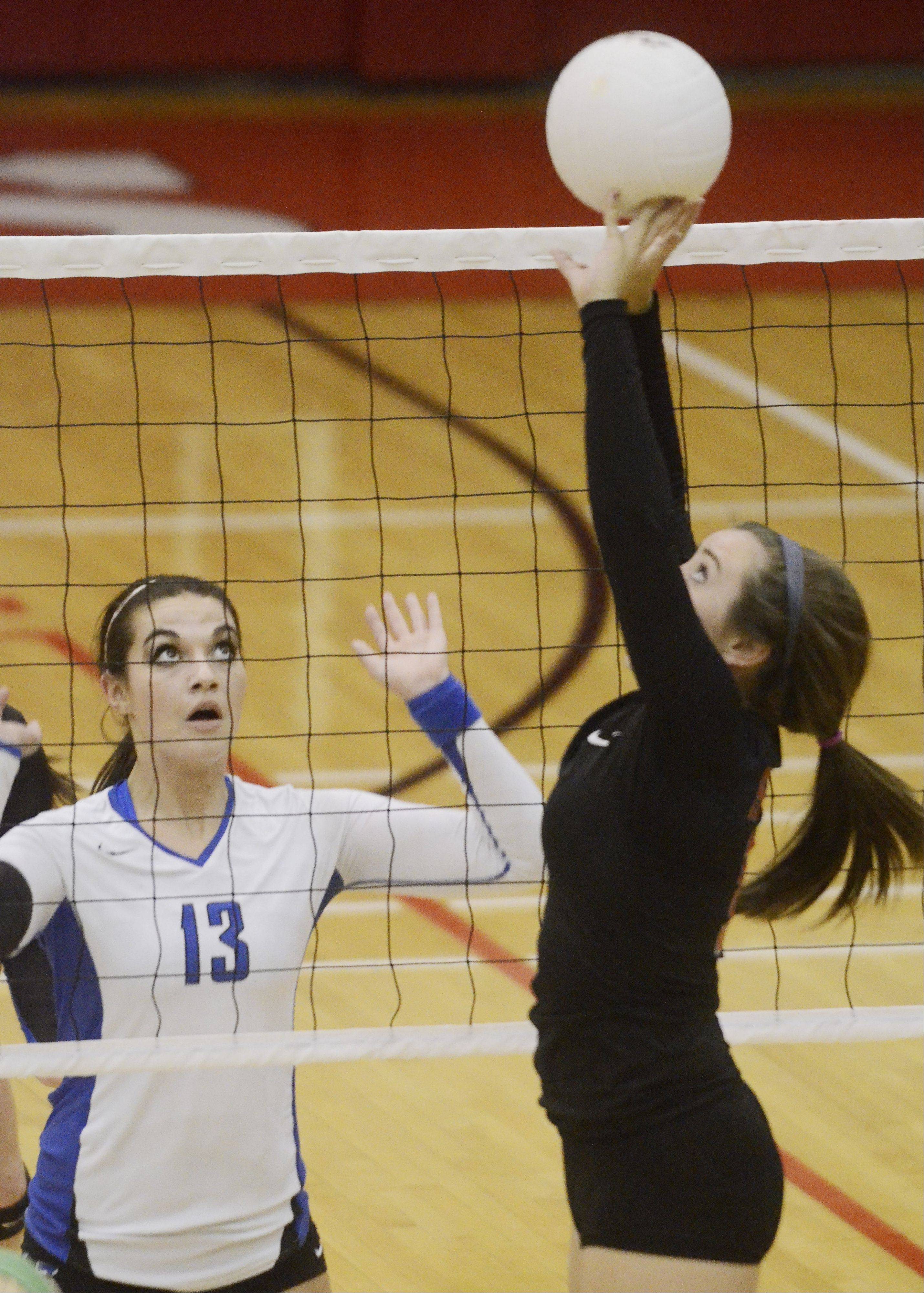 Palatine's Sarah Schiffner, right, sets the ball as Lake Zurich's Mallory Parsons anticipates a block during Wednesday's game.