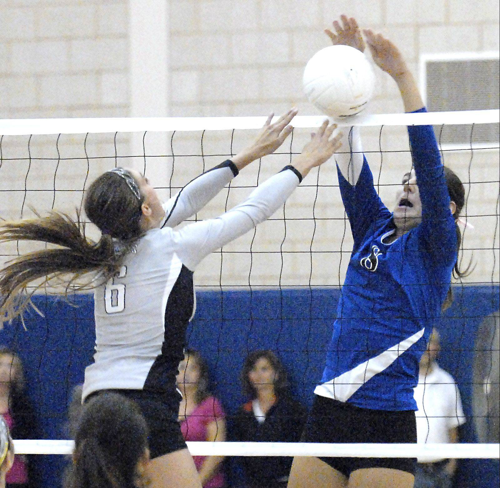 Kaneland's Lyndi Scholl's hit is blocked by Geneva's Jess Wicinski in he third match on Wednesday, September 26.