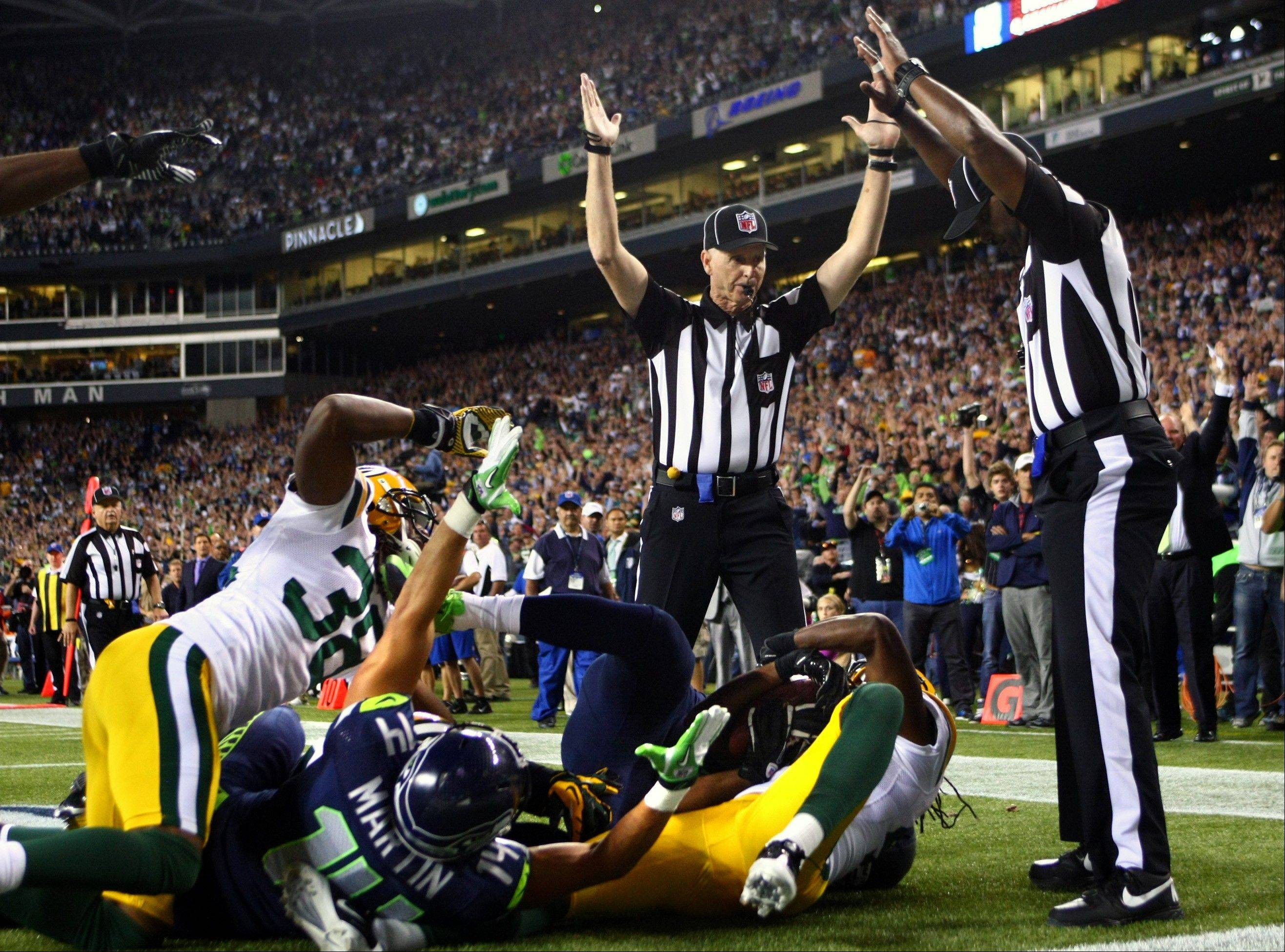 Officials signal a touchdown and a touchback after Seattle Seahawks wide receiver Golden Tate pulled in a last-second pass for a touchdown from quarterback Russell Wilson to defeat the Green Bay Packers 14-12 Monday night. On Wednesday, the NFL and the referees' union appeared on the brink of ending a three-month stalemate, two days after the Green Bay Packers lost a game they would have won if not for a less adept crew of replacement officials.