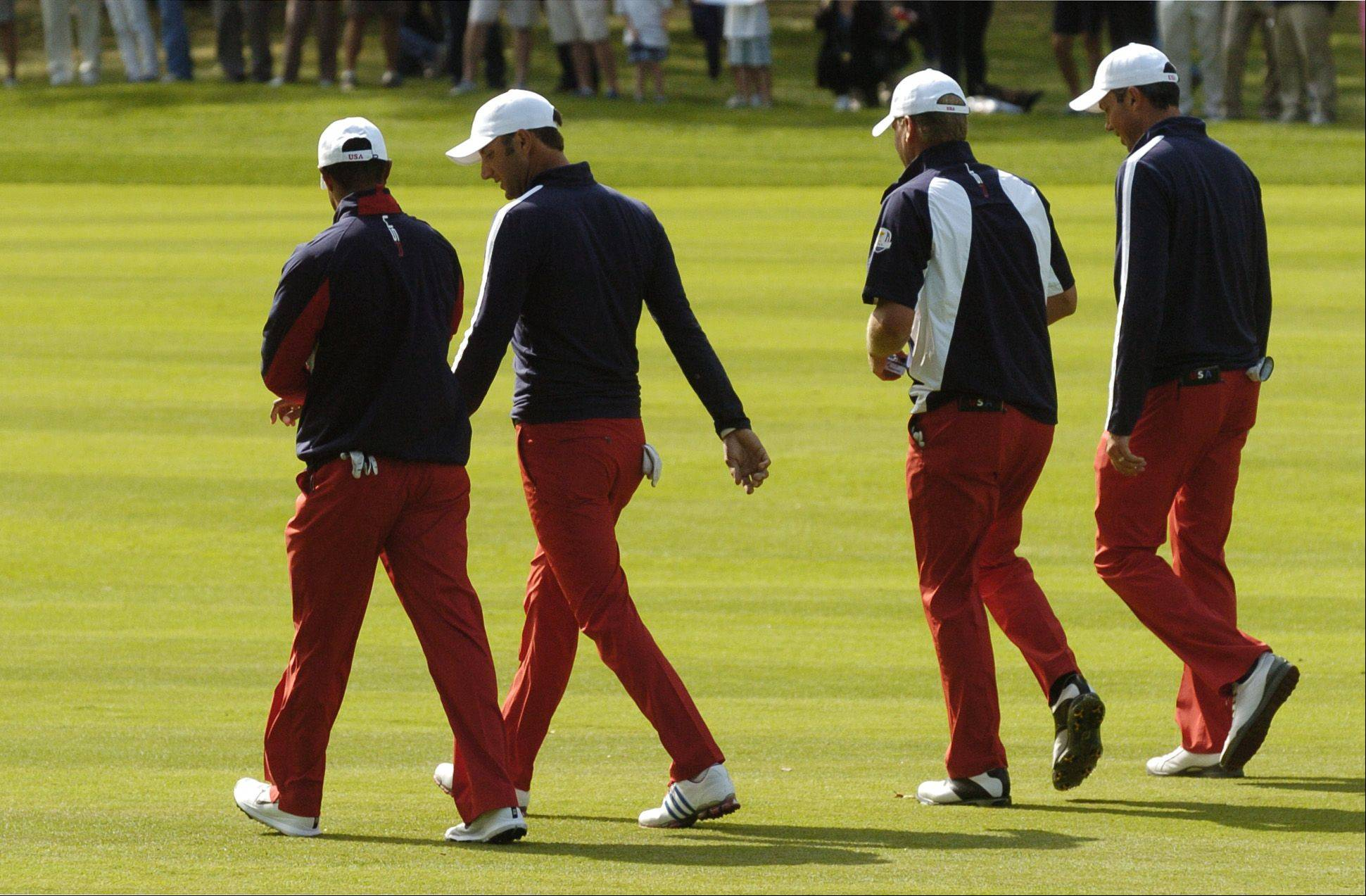 Team United States walks up the ninth fairway .