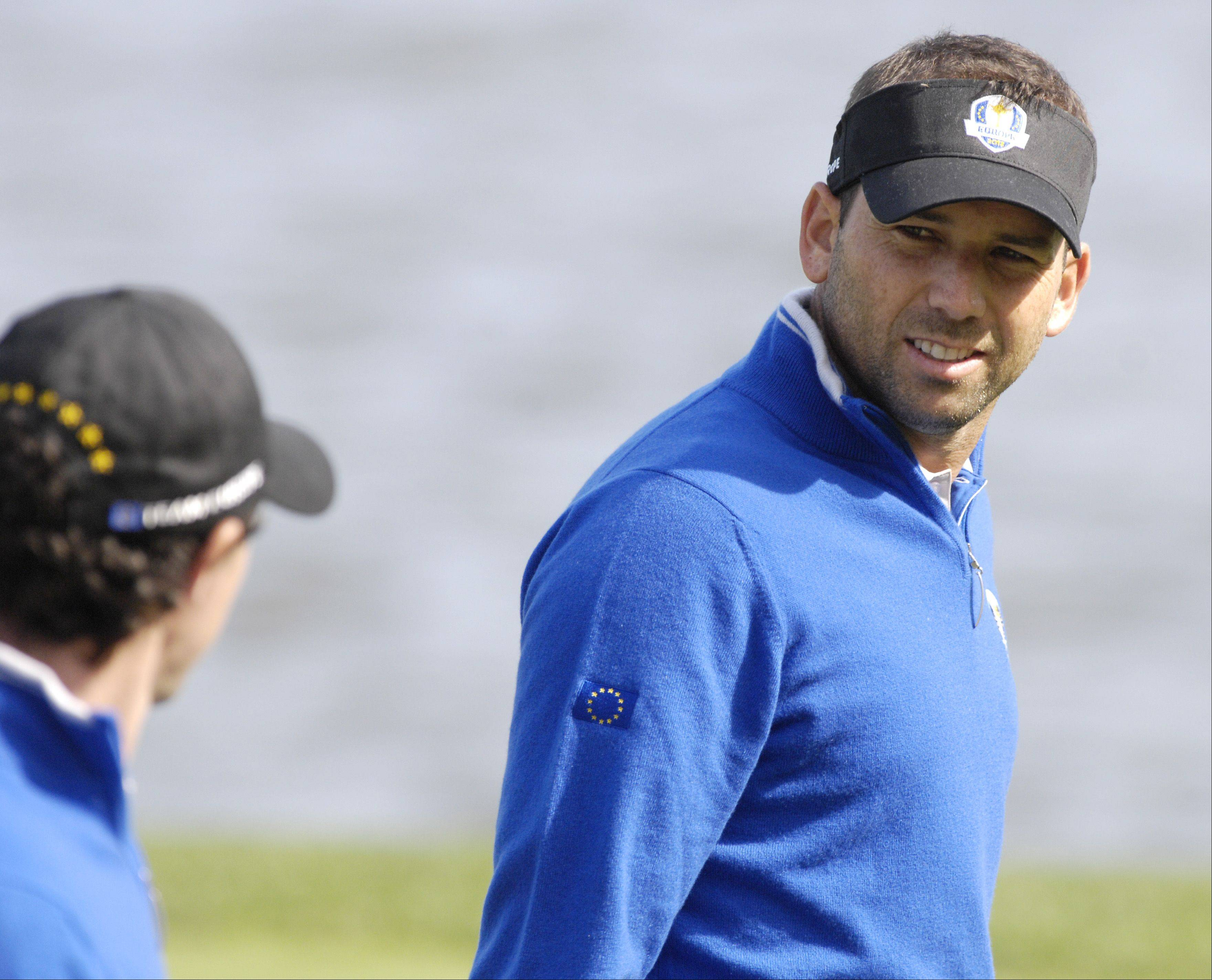 Team Europe teammates Sergio Garcia, right and Rory McIlroy talk while working the second green.