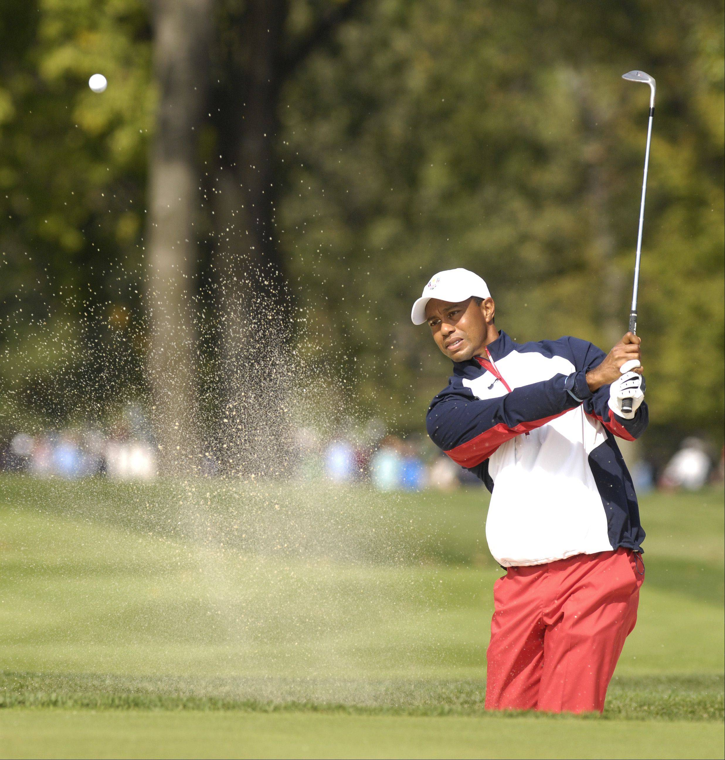 Tiger Woods of Team USA chips the ball out the sand.