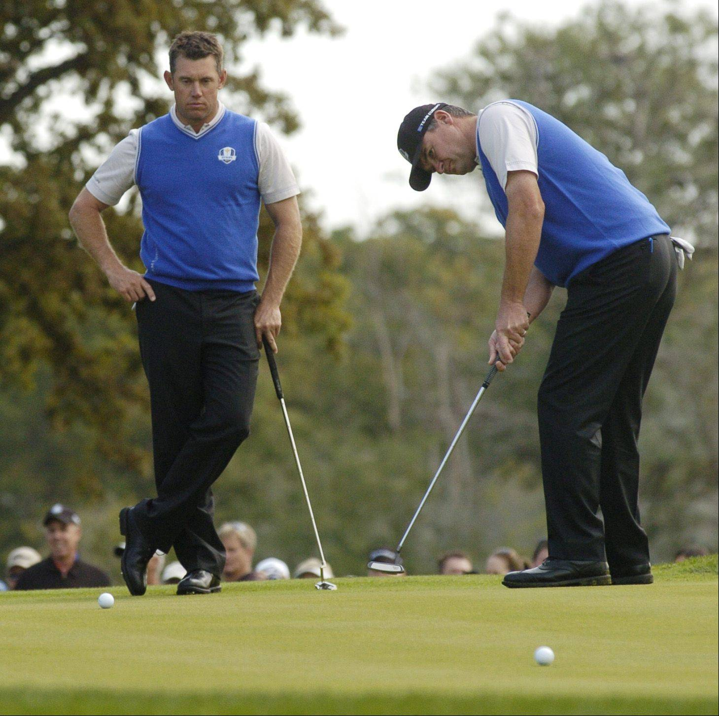 Lee Westwood of Team Europe and Paul Lawrie of Team Europe practice their putts on the first green.