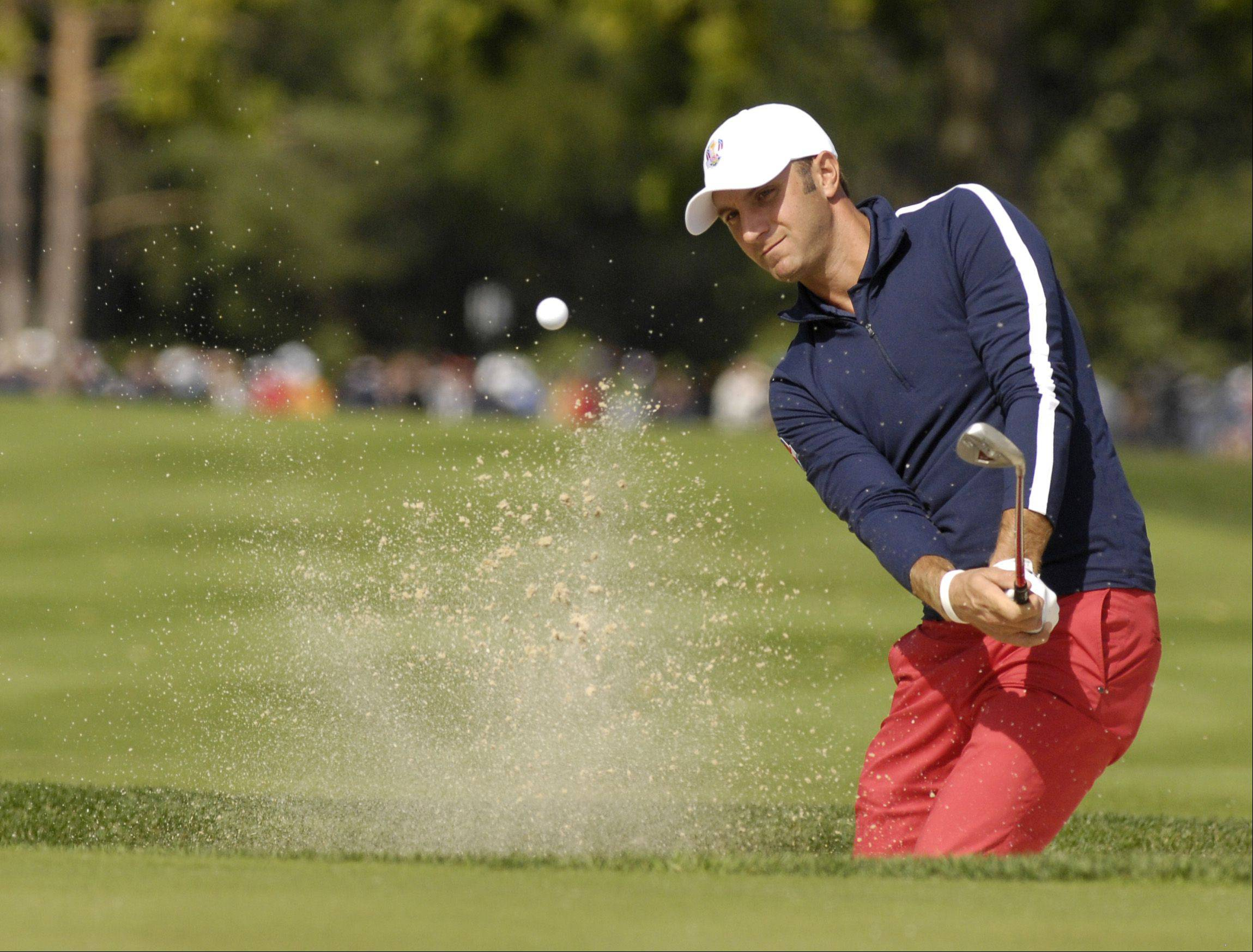 Dustin Johnson of Team USA chips the ball out of the sand.