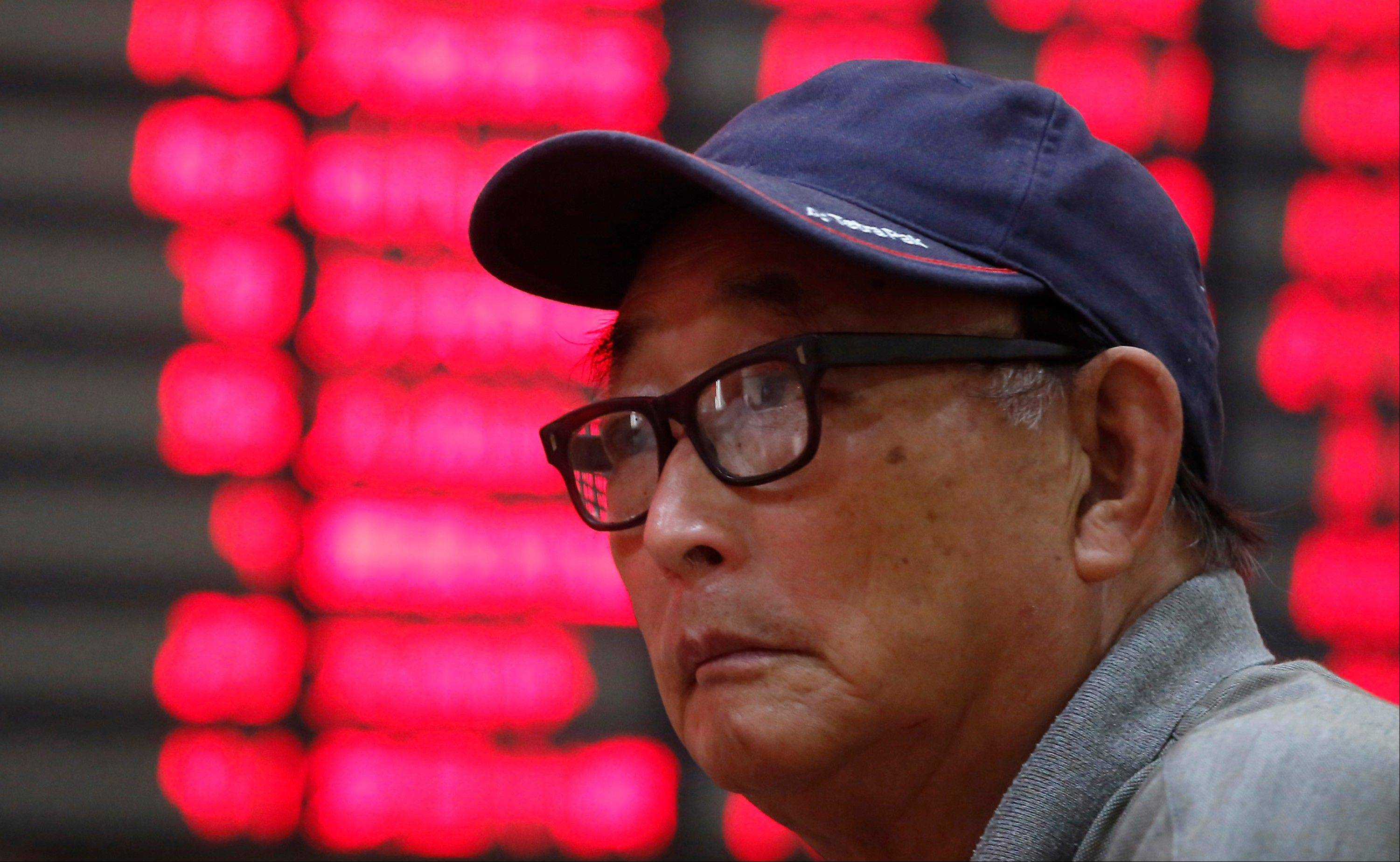 An investor looks at the stock price monitor at a private securities company Thursday in Shanghai, China.