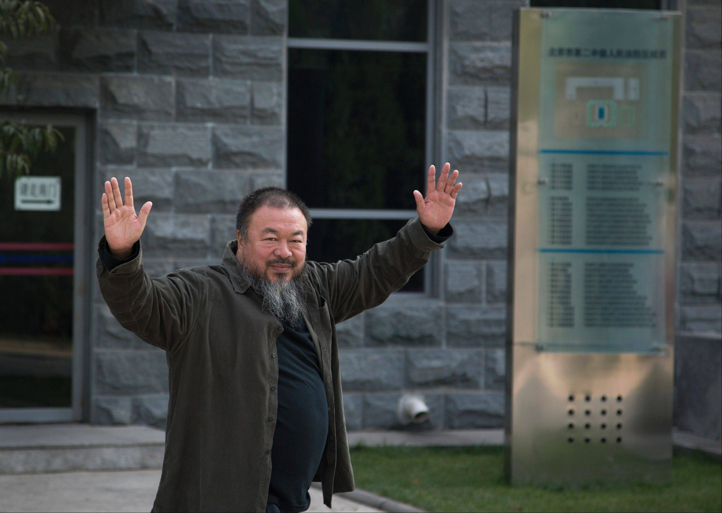 Chinese activist artist Ai Weiwei waves to the journalists as he arrives to the Beijing No. 2 People's Intermediate Court in Beijing Thursday, Sept. 27, 2012. Chinese authorities on Thursday rejected Ai's second appeal of a $2.4 million tax fine.