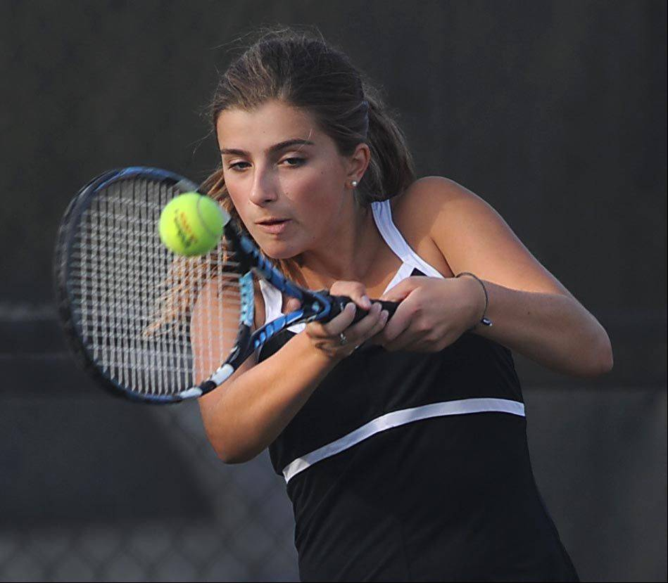 St. Charles East's Haydyn Jones returns a two-handed shot as she plays #1 Doubles with Kelsie Roberton against Batavia's Amelia Cogan and Jenny Mizikar Thursday in St. Charles.