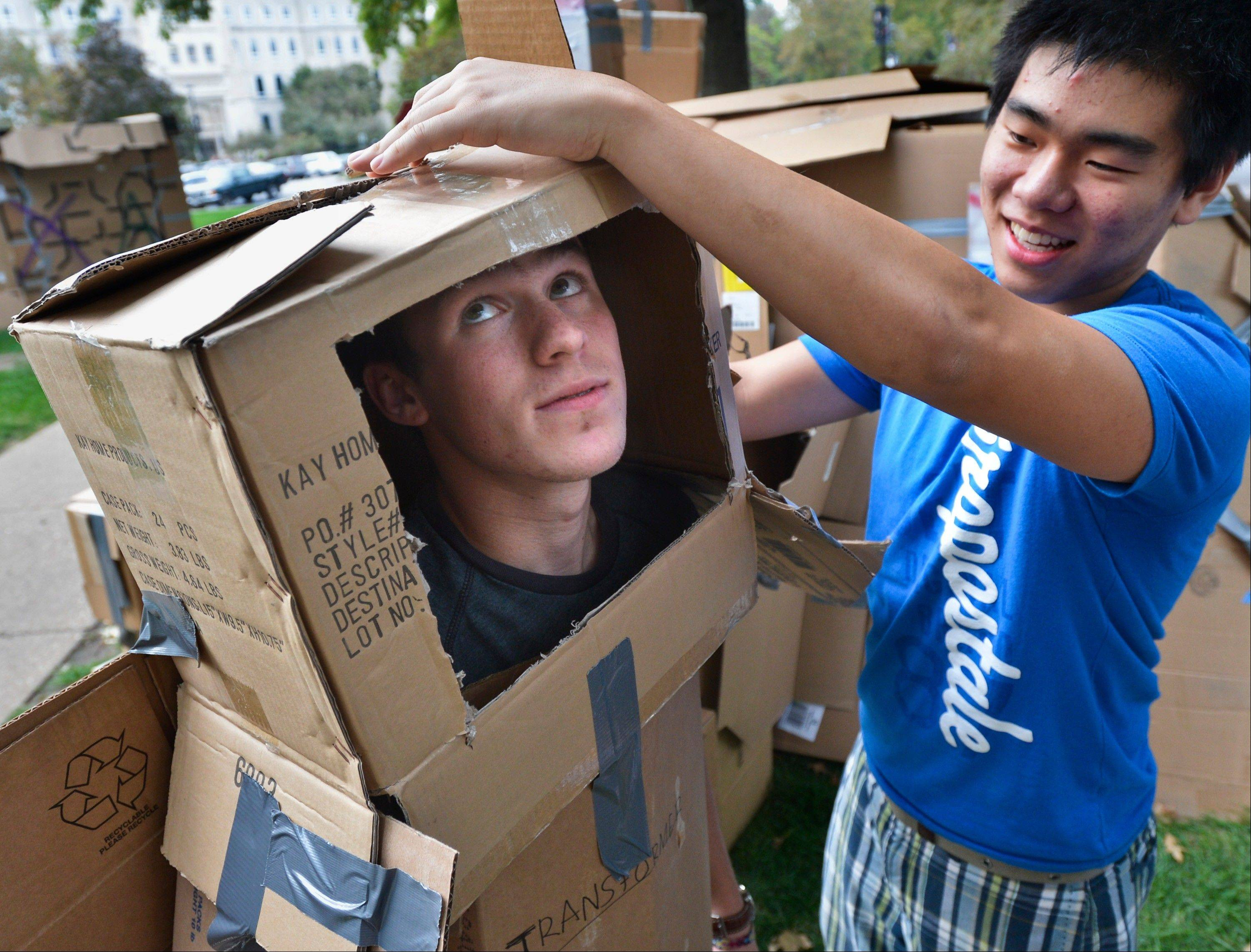 "Bradley University freshman Jeremy Lee, right, tapes a cardboard box on top of freshman Zach Singleton, turning him into ""cardboard man"" during Wednesday's annual Habitat for Humanity's fundraiser, ""Shack-a-Thon"" on the Bradley campus in Peoria. Students built cardboard homes and later slept overnight in them to experience the plight of the homeless."